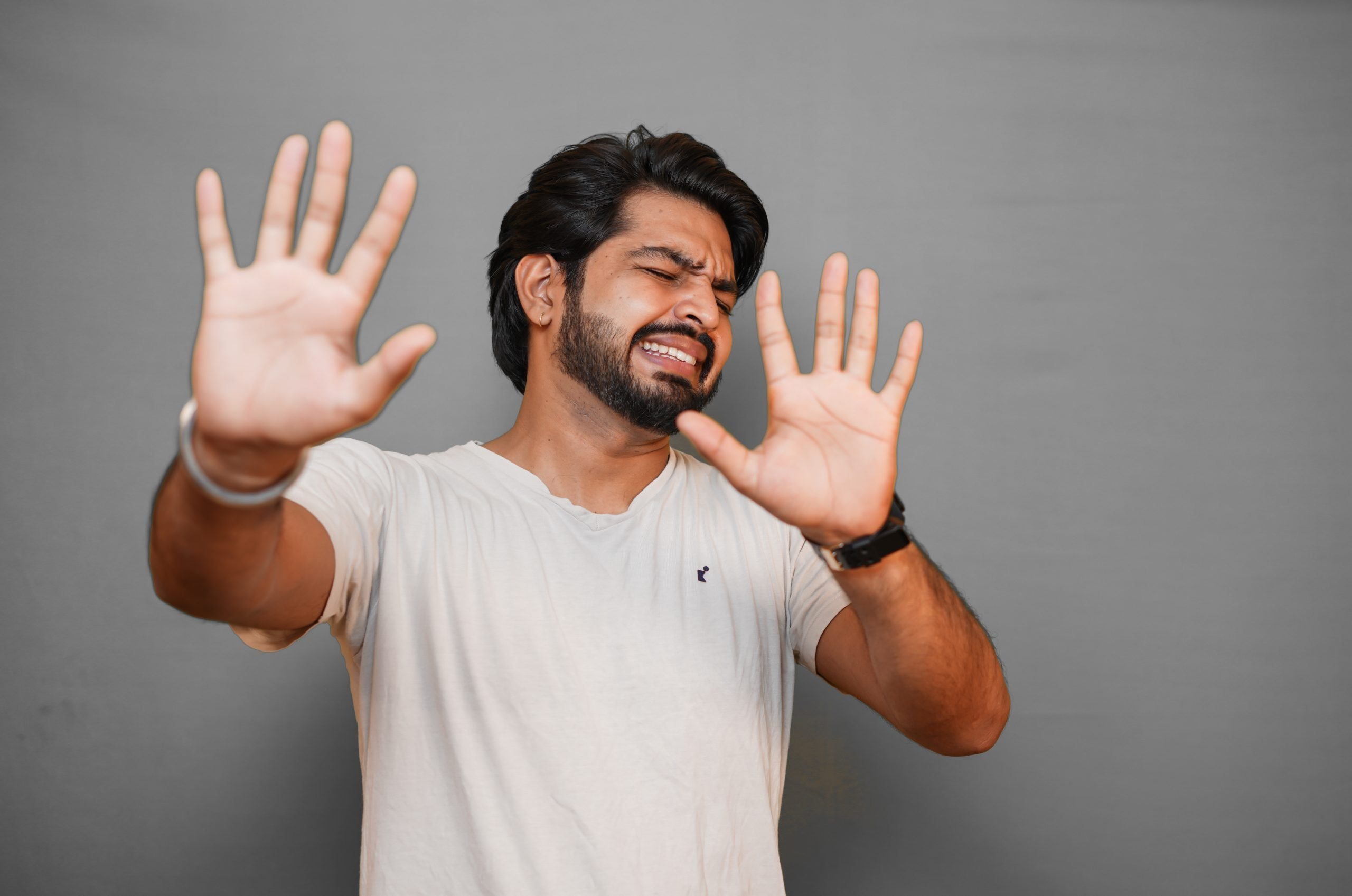 Young indian with disgusting expression showing denial with hands