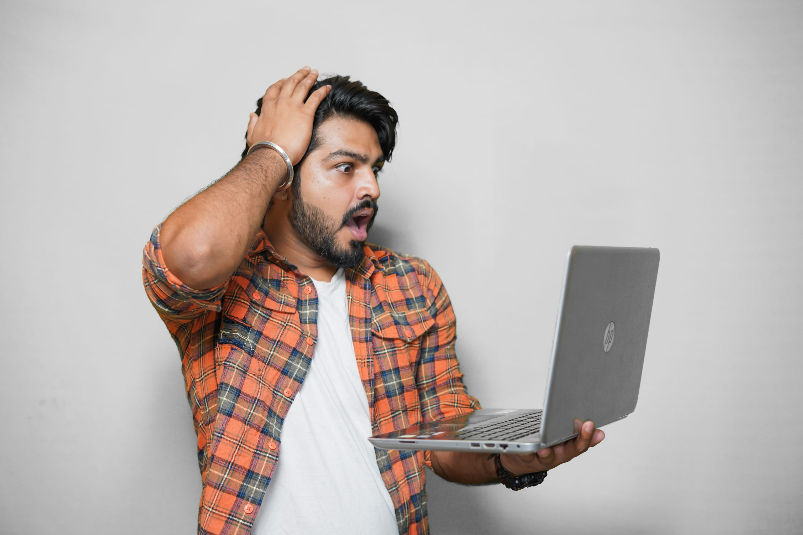 Young man looking shocked seeing something on Laptop