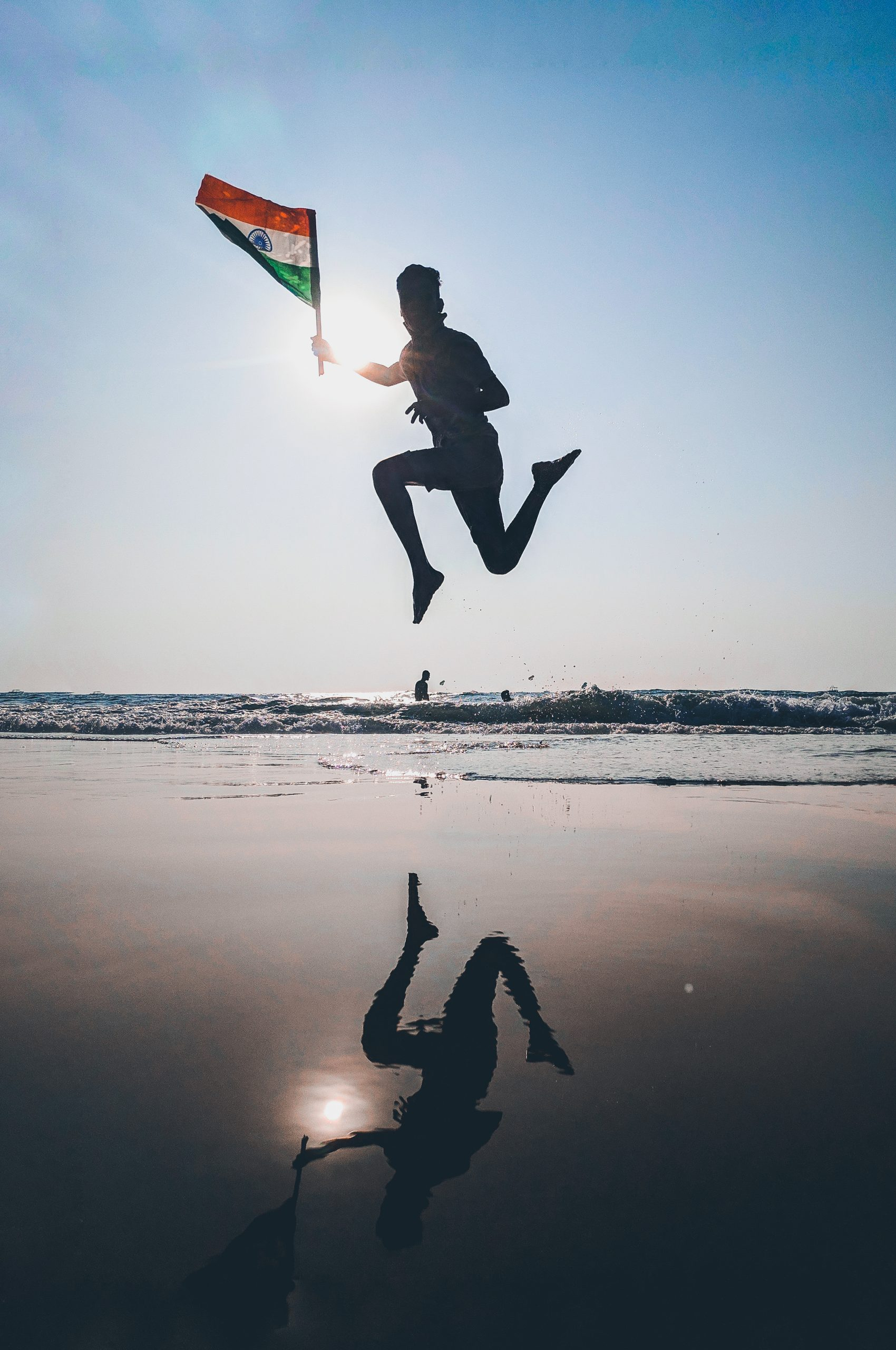 boy jumping with indian flag at sea