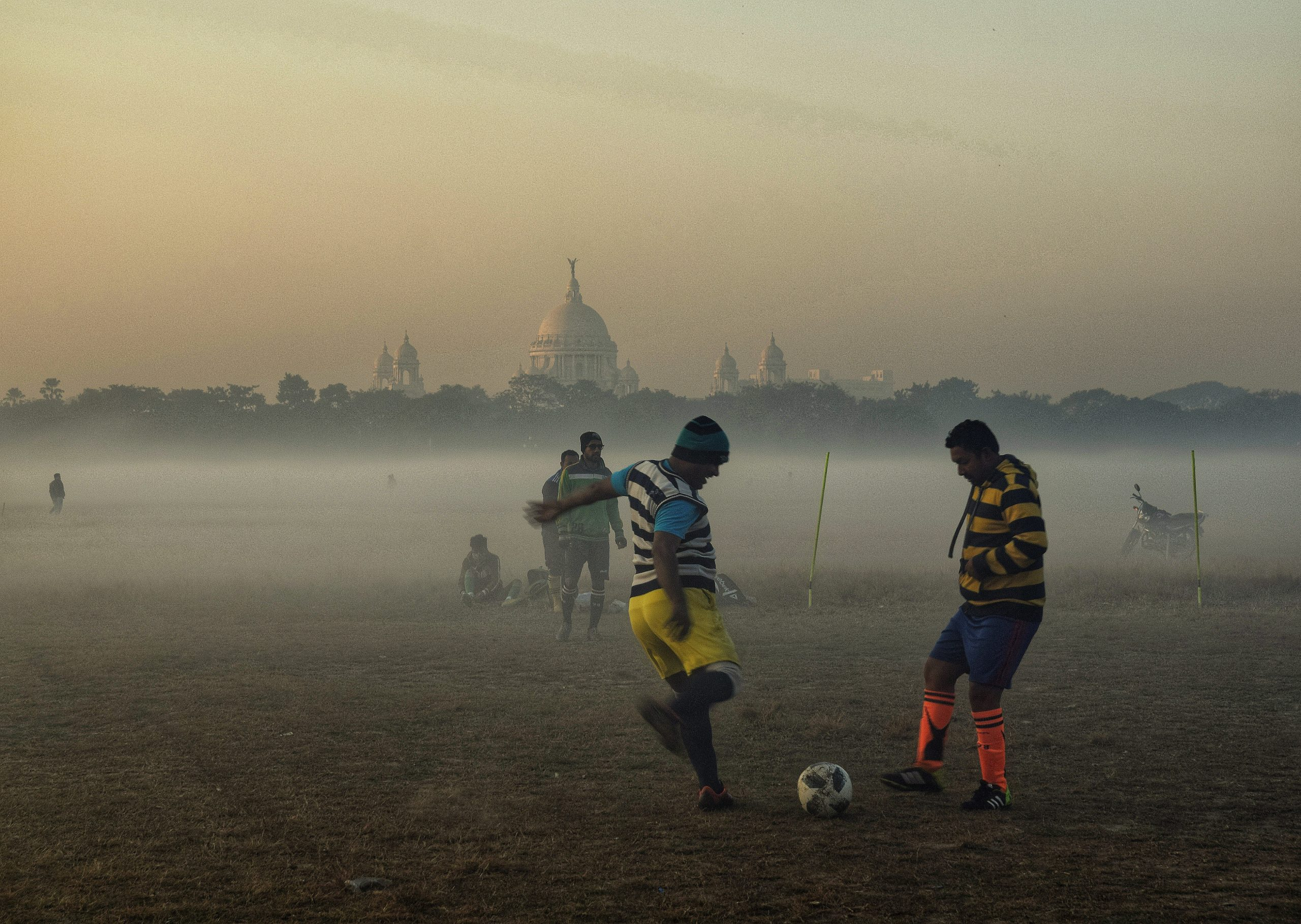 Boys playing football in a ground
