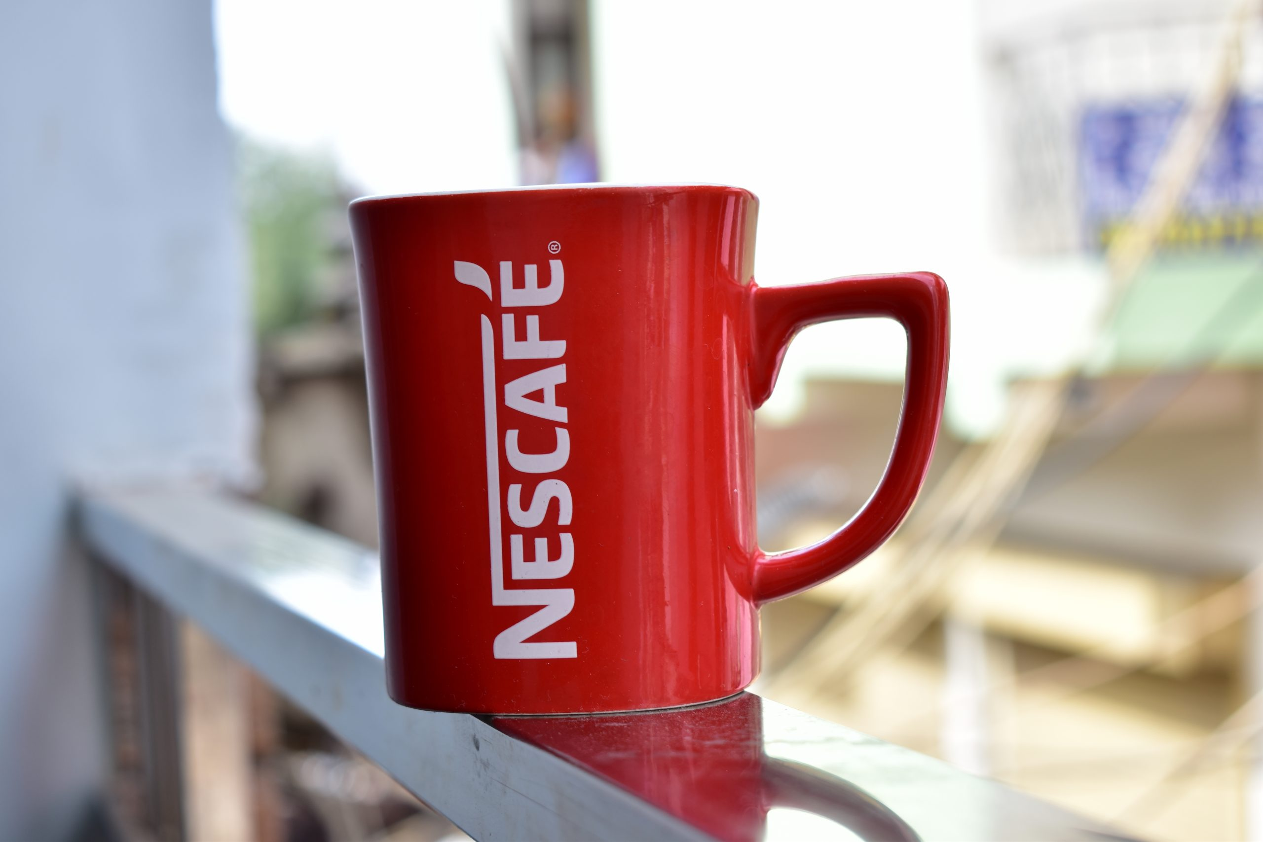 Red Nescafe cup on a ledge