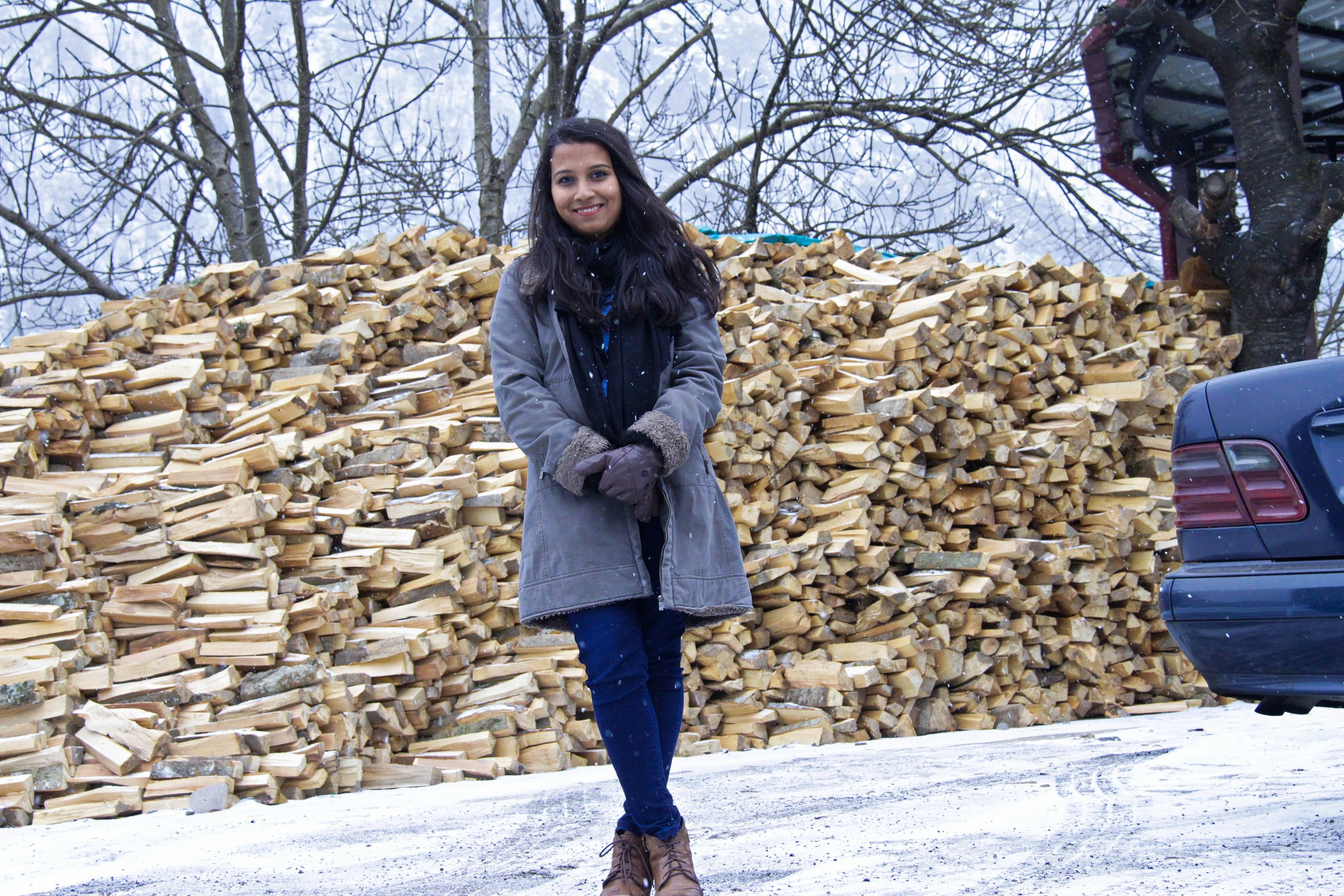Woman standing by a woodpile