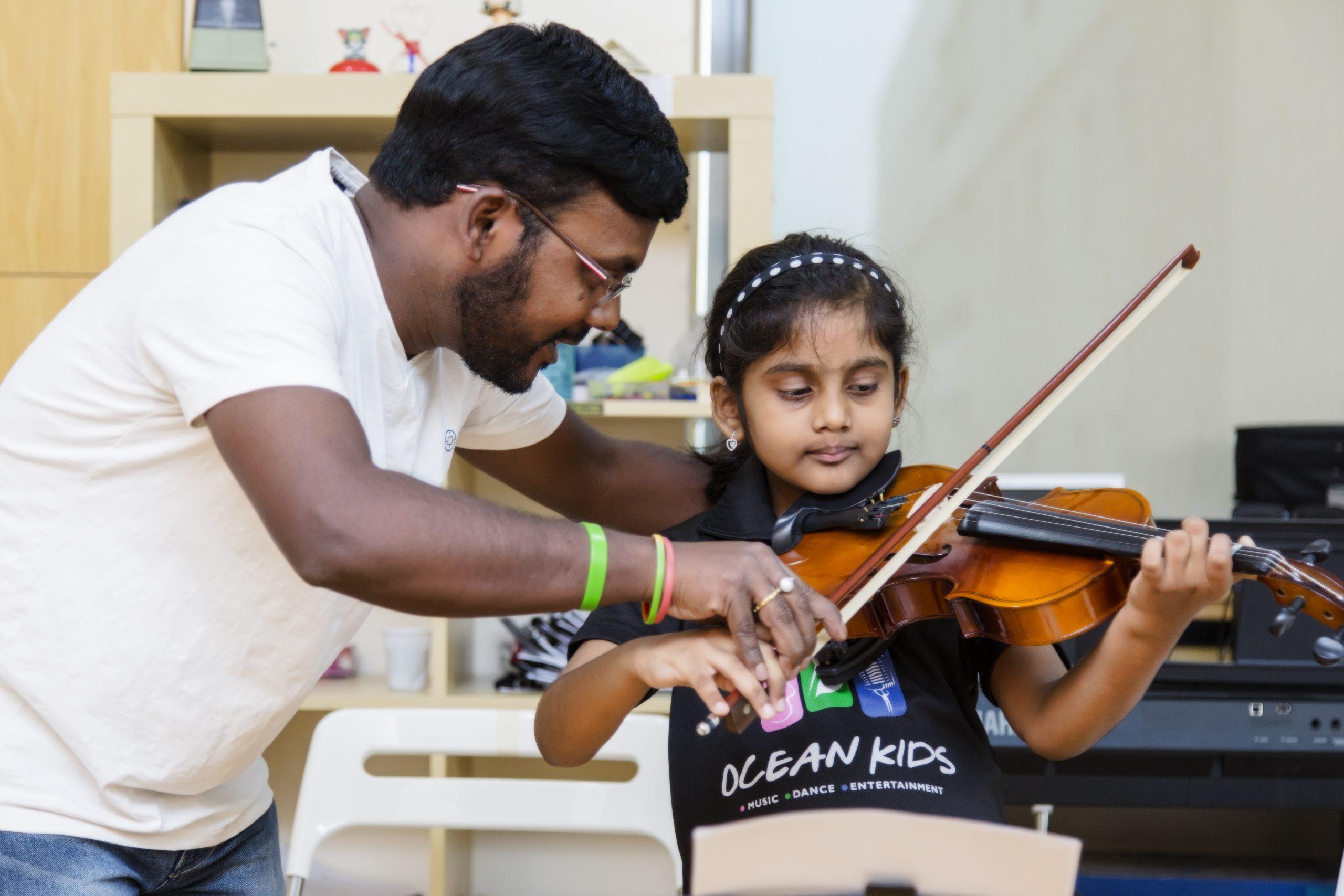 girl learning violin from teacher
