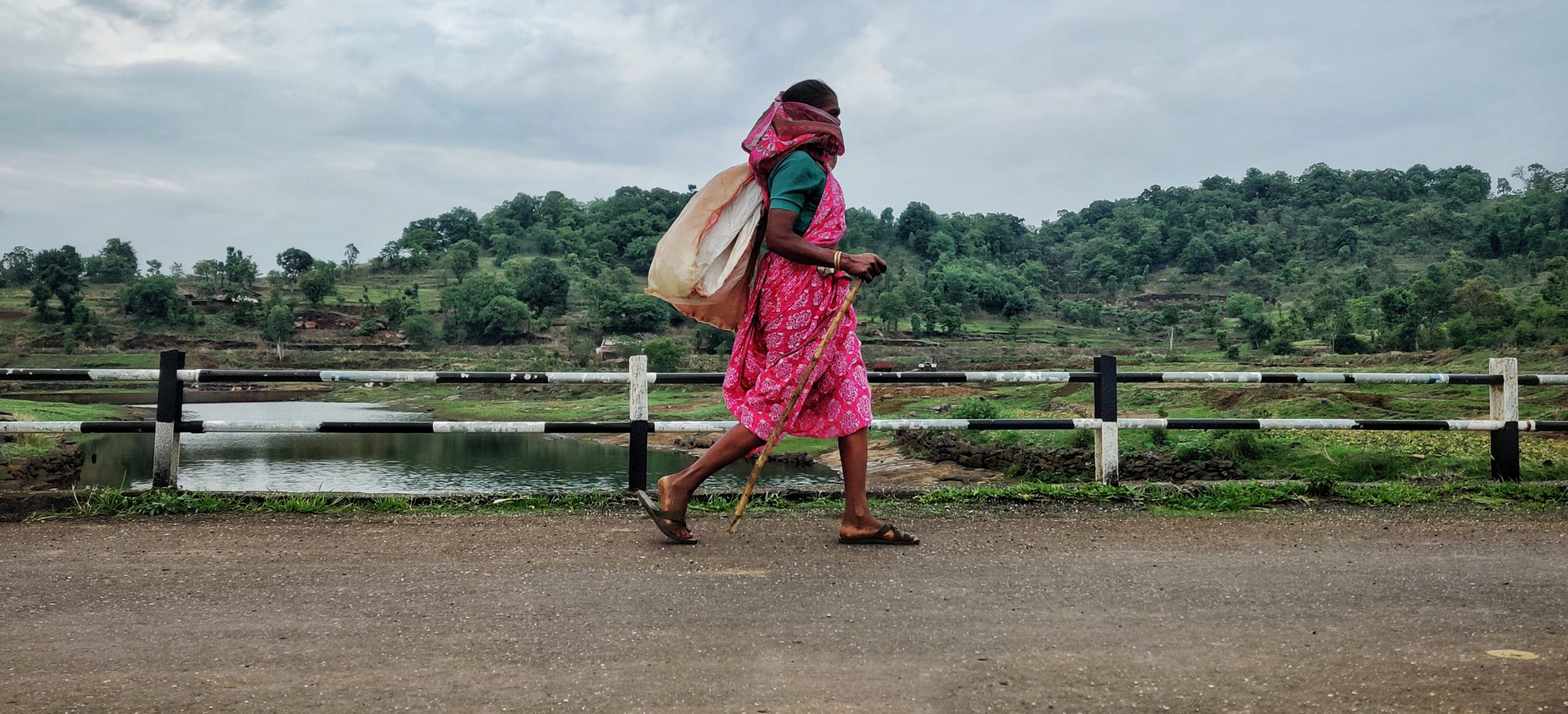 Woman walking on a road and watching the nature.