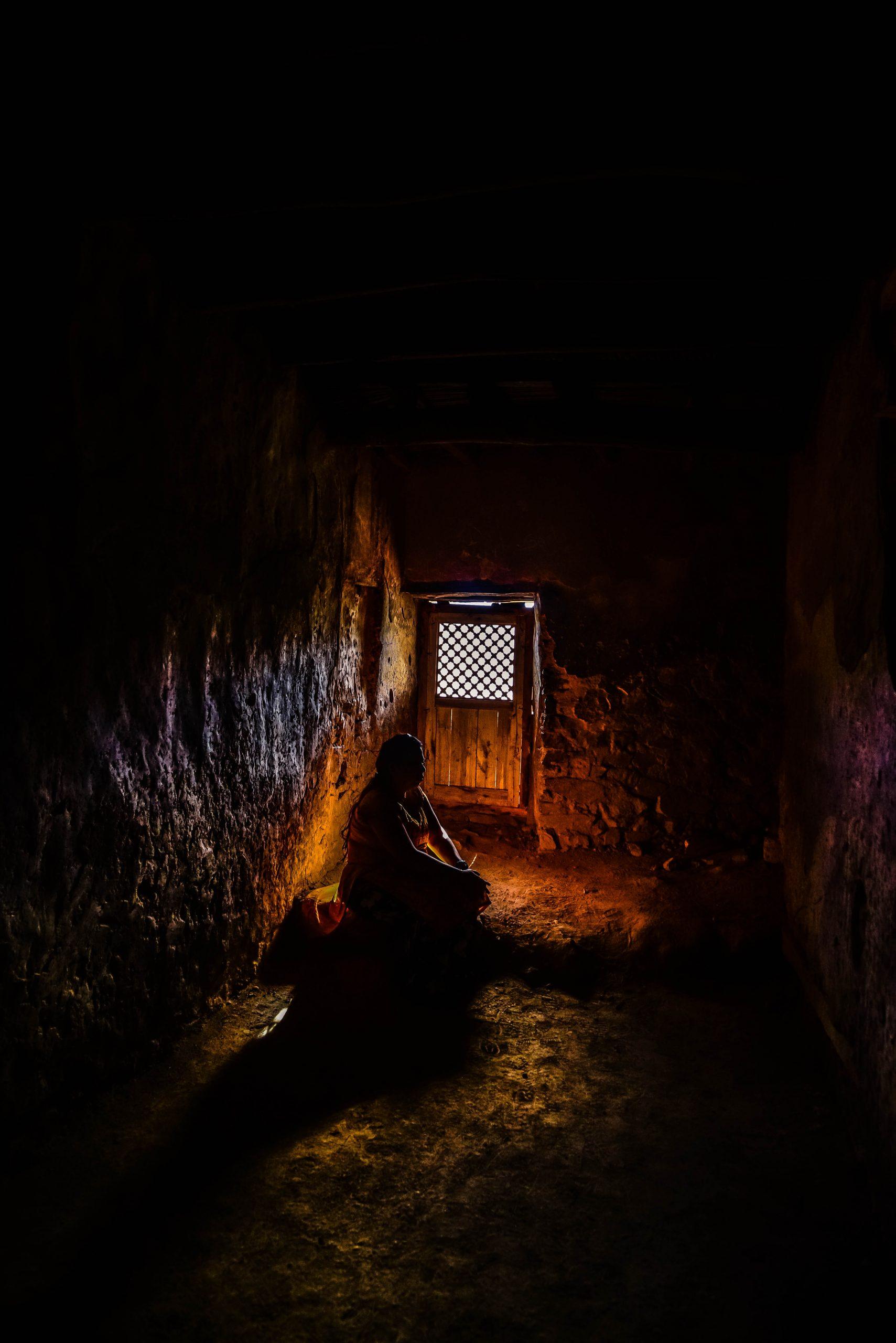 A woman sitting in a dark room.
