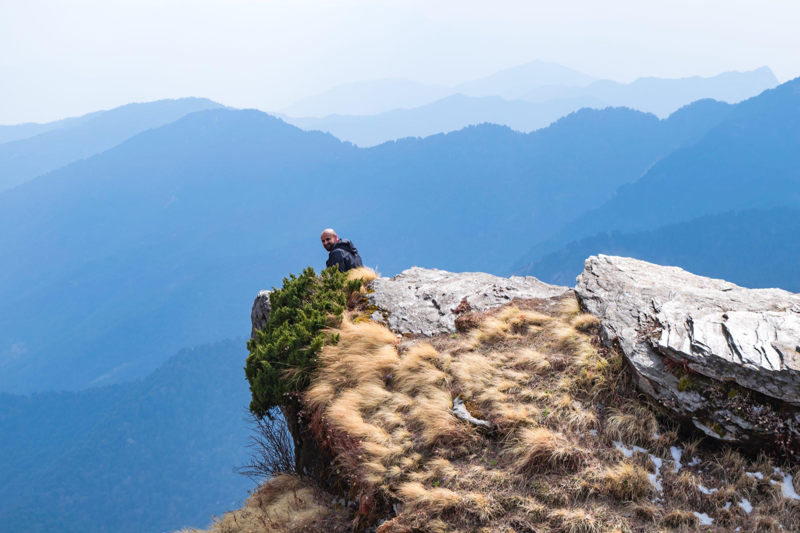 man sitting on edge of a mountain