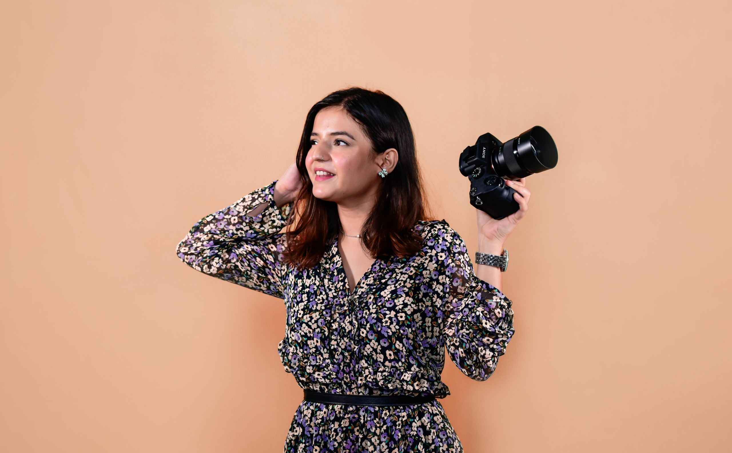 A girl holding a camera happily.