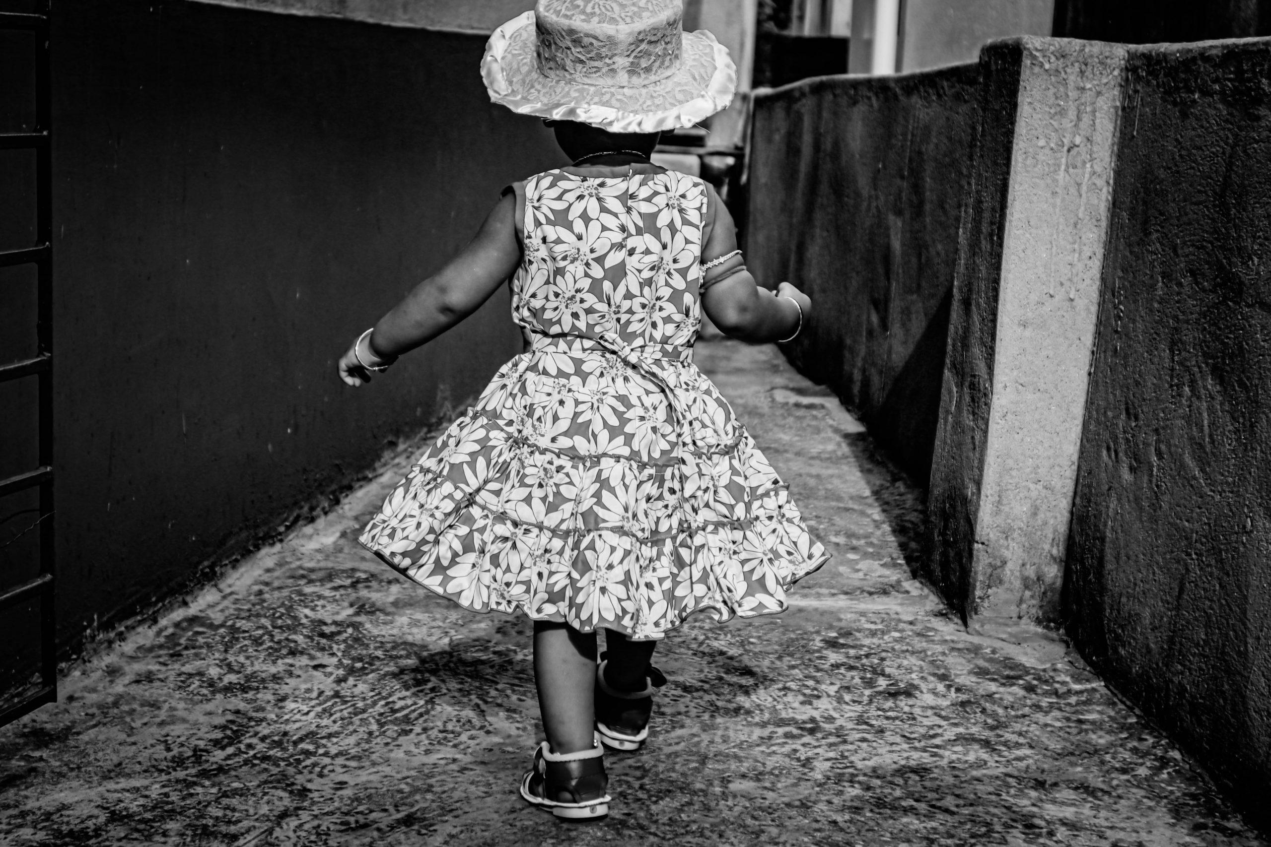 A baby girl walking in a street