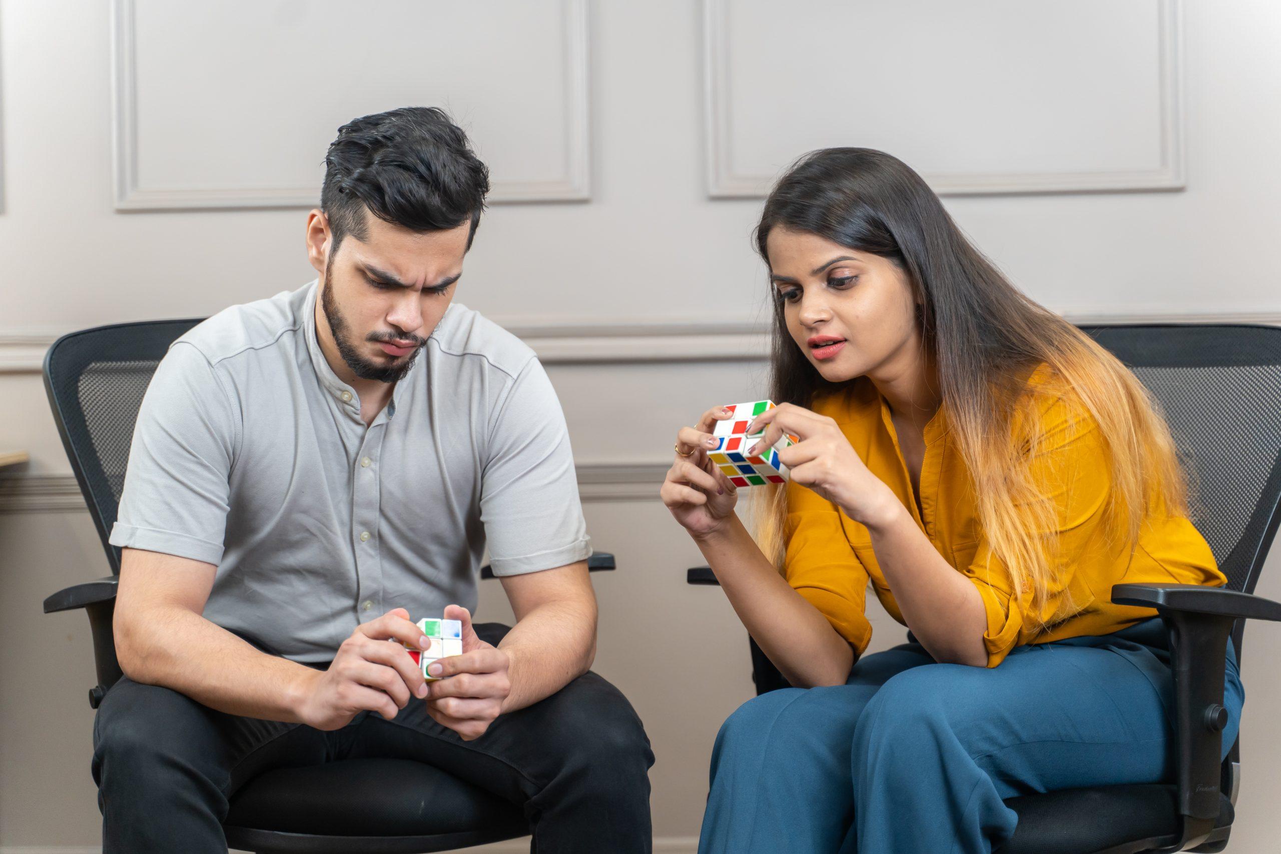 A girl and boy solving rubik cube