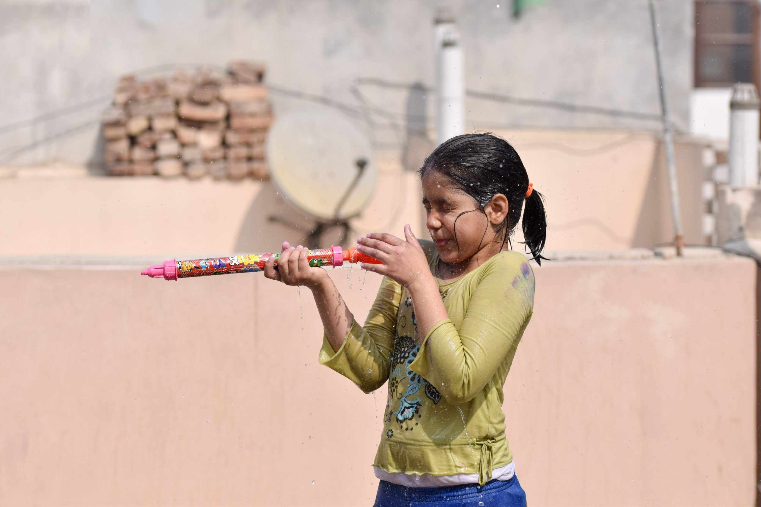 A girl playing with water gun on Holi