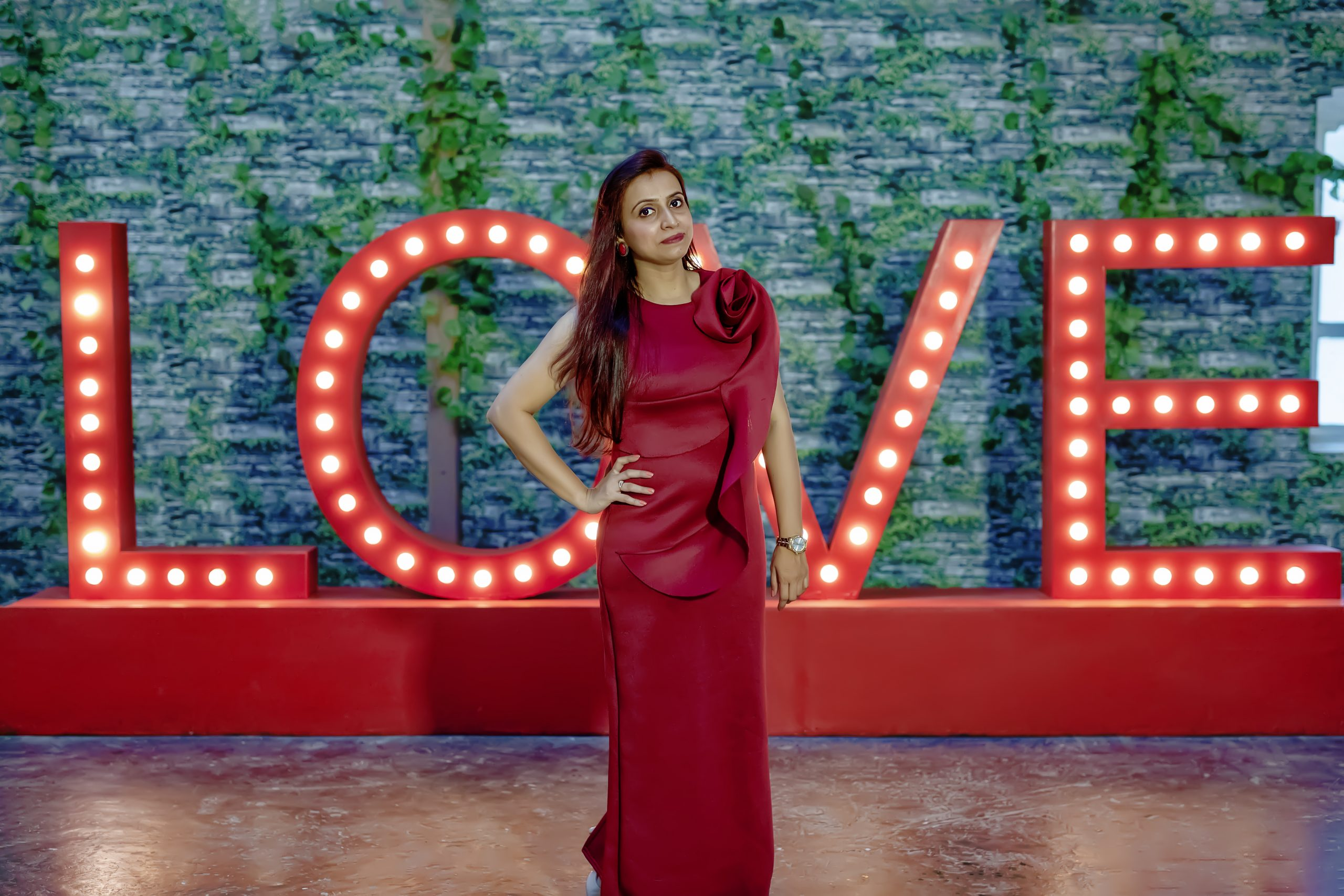 A lady posing in front of 'Love' sign