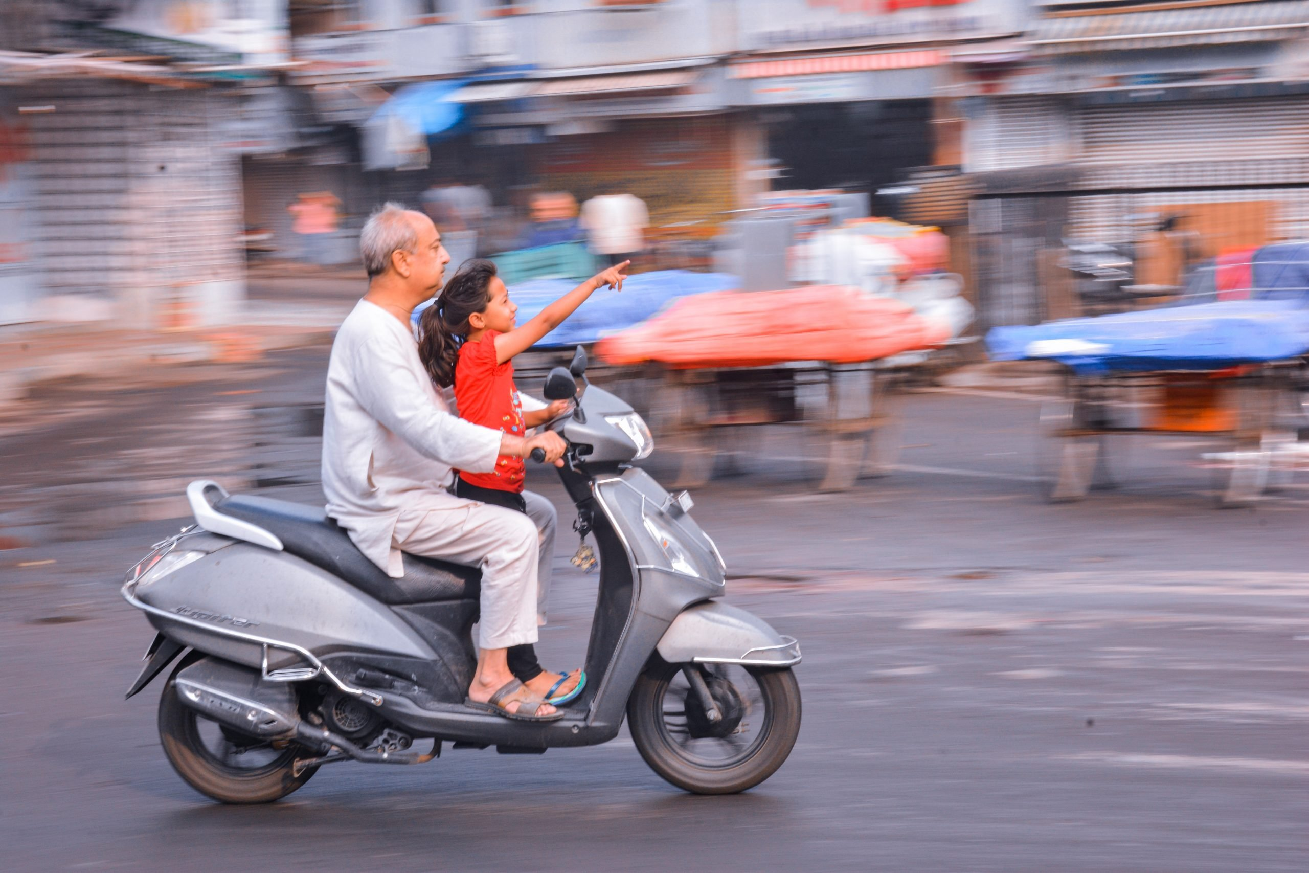 A little girl and grandfather on a scooter