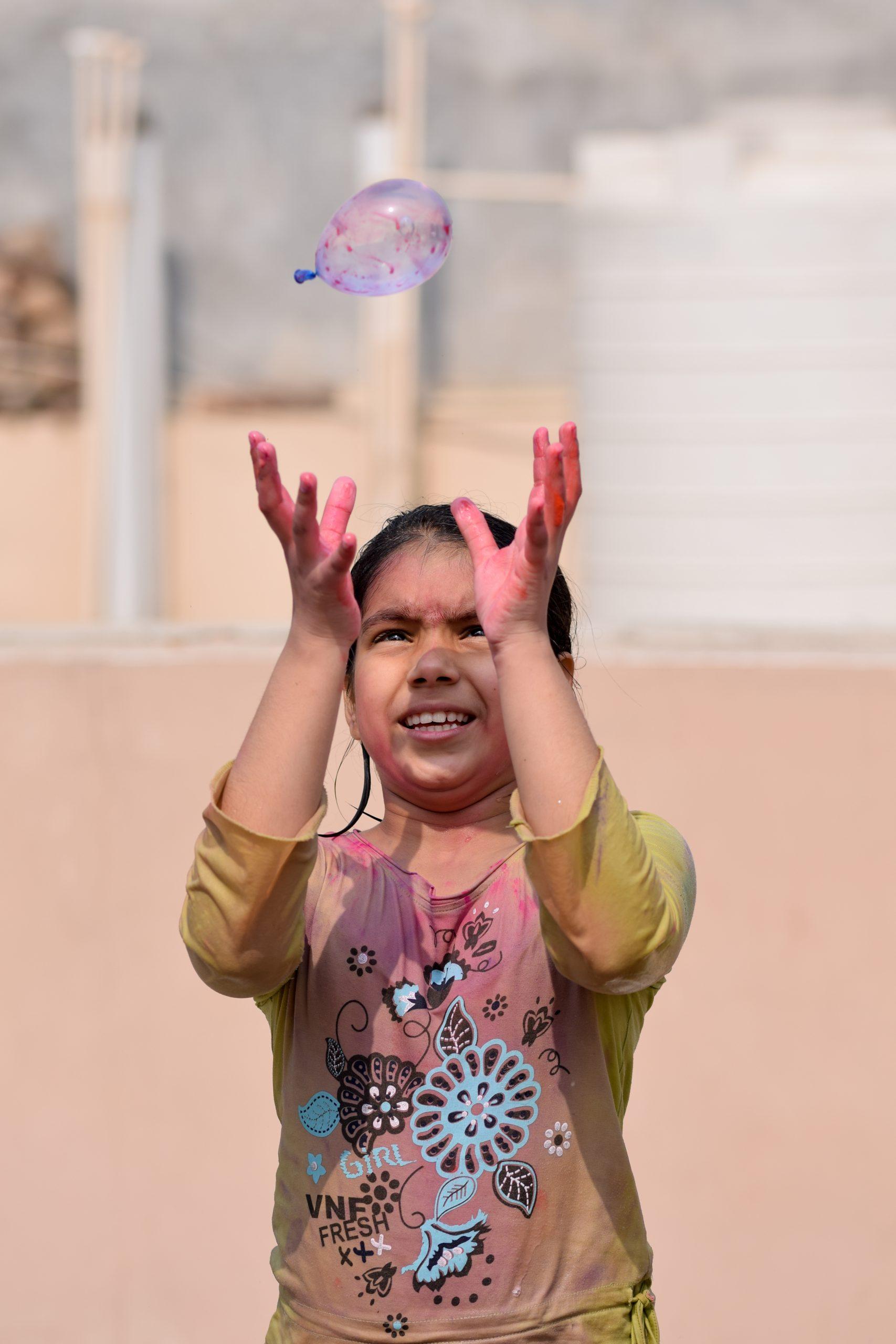 A little girl catching water balloon