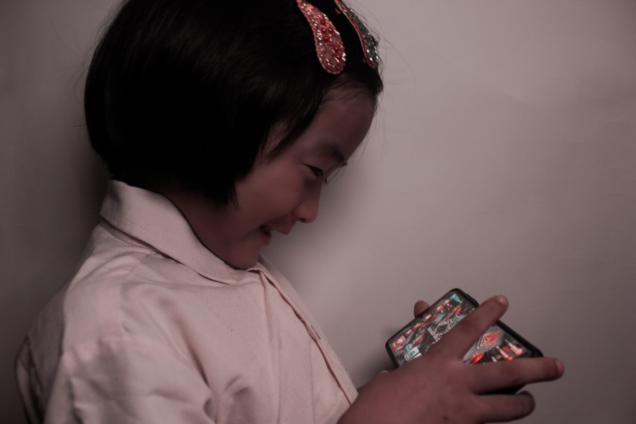 A little girl playing mobile game