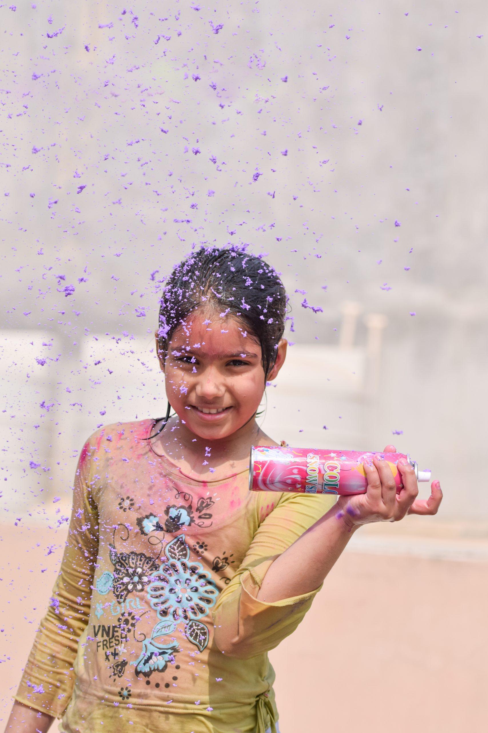 A little girl using foam spray on holi