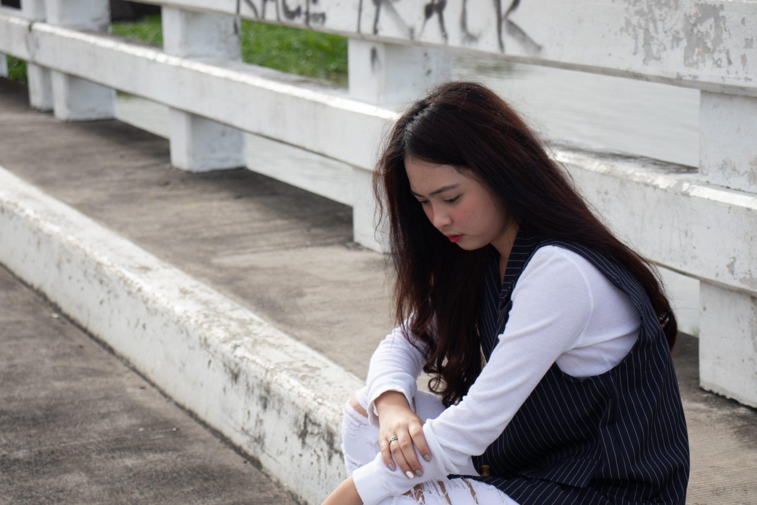 A sad girl sit on a bridge