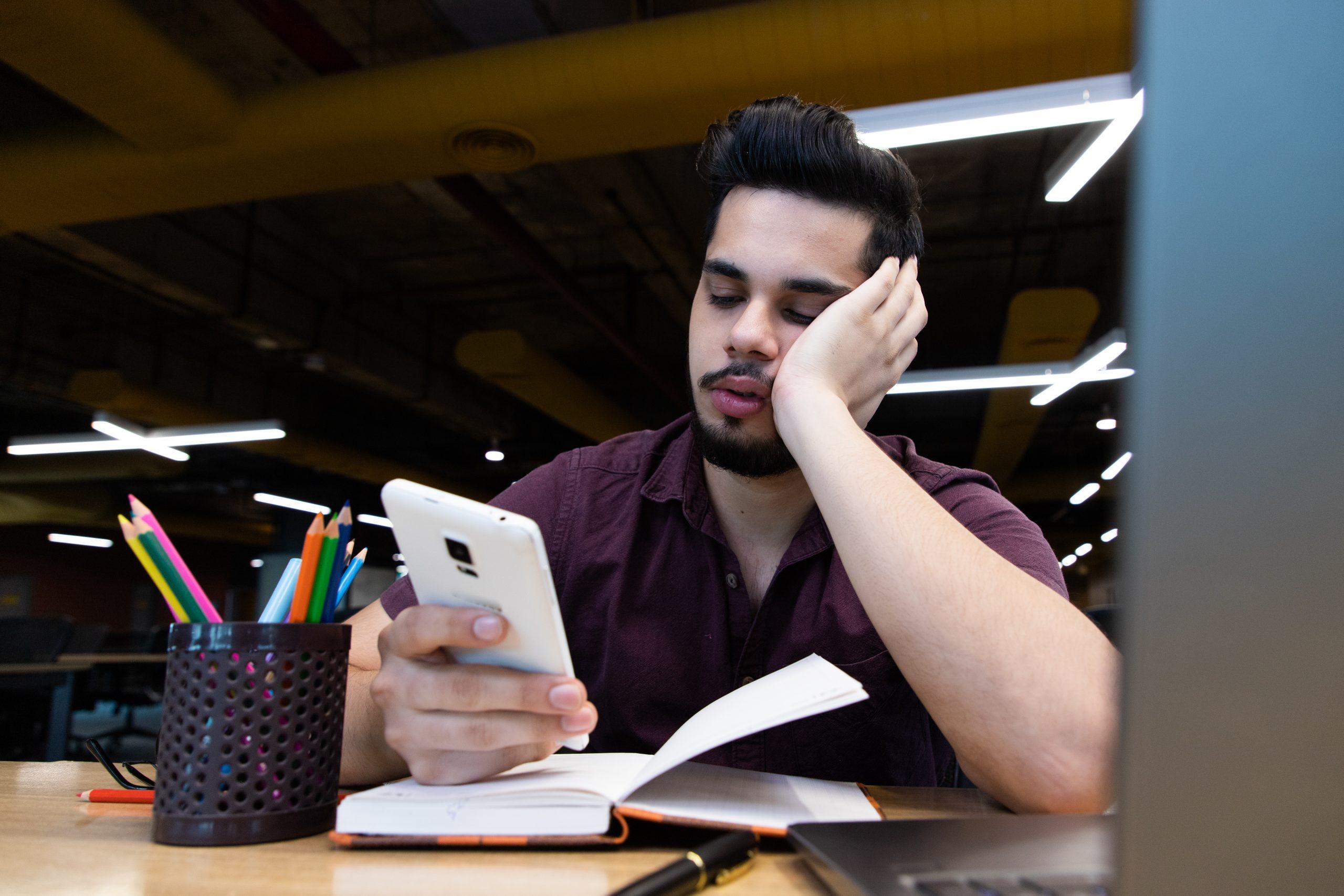 A sleepy man using tablet