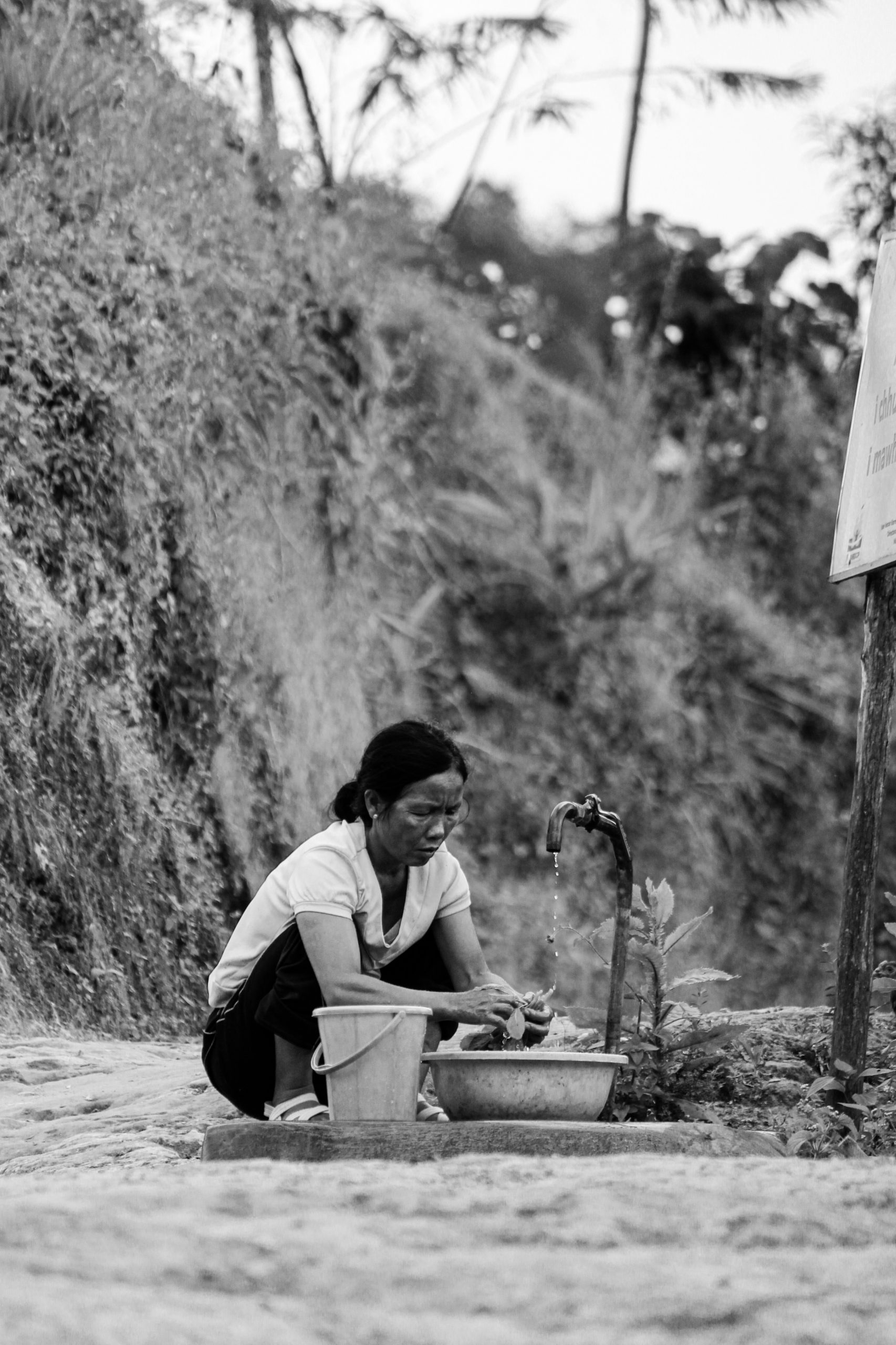 A woman washing vegetables with tap water