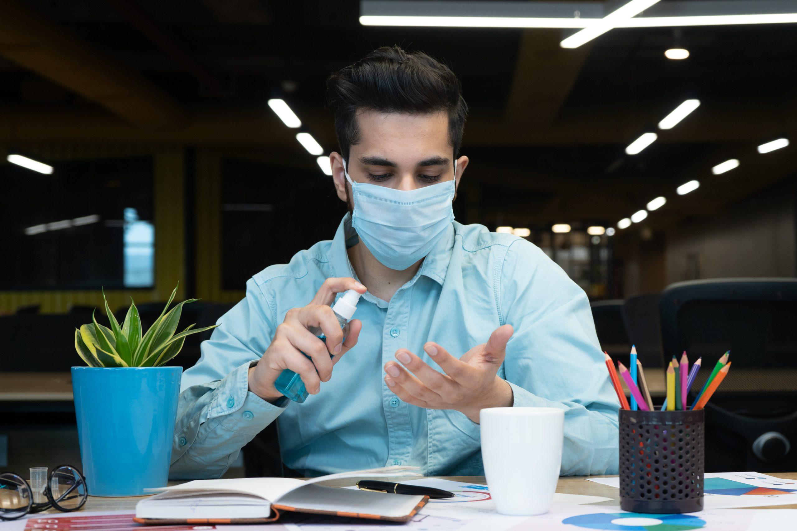 An employee sanitizing his hands
