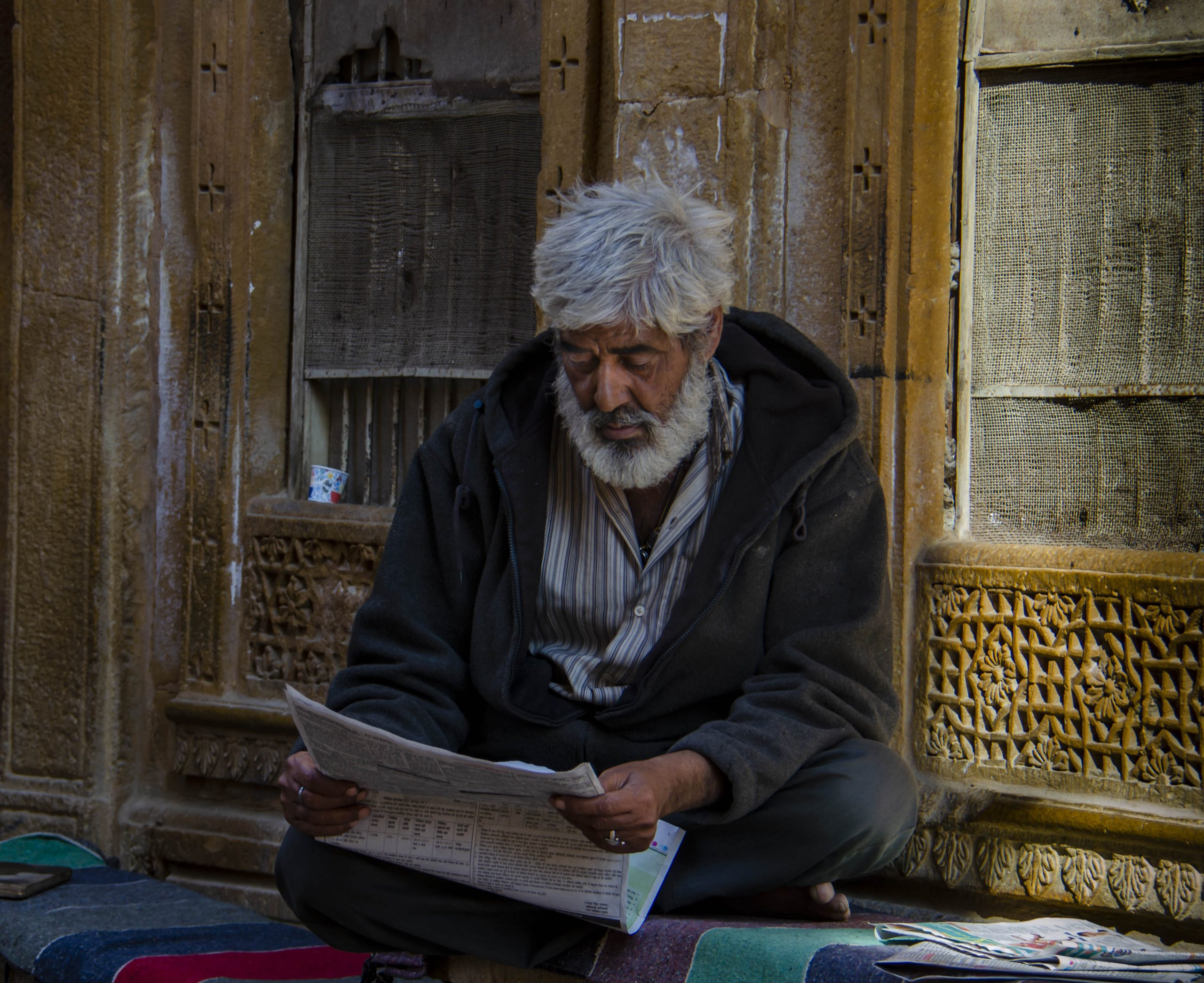 An old man reading newspaper