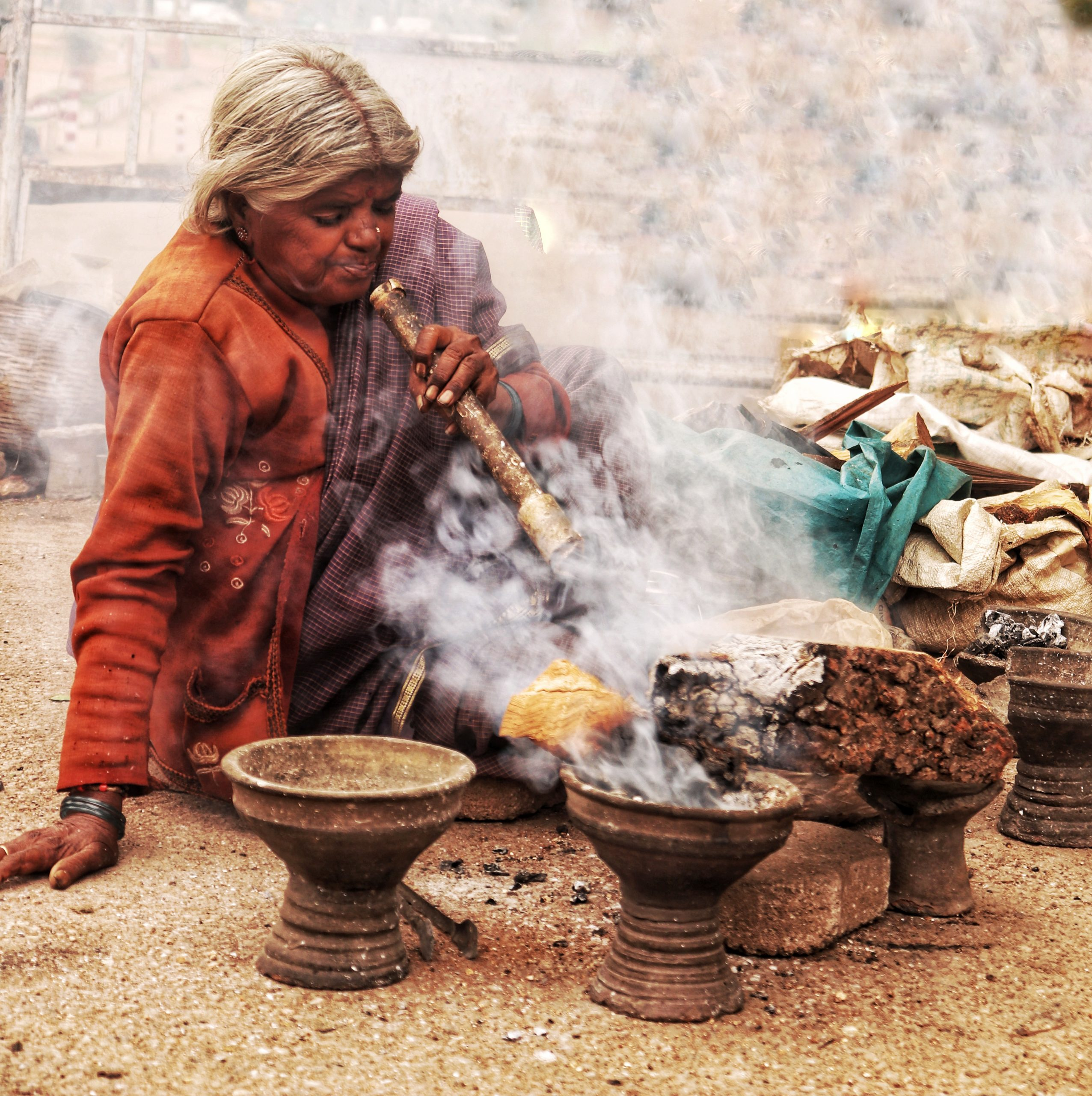 An old woman blowing air with pipe