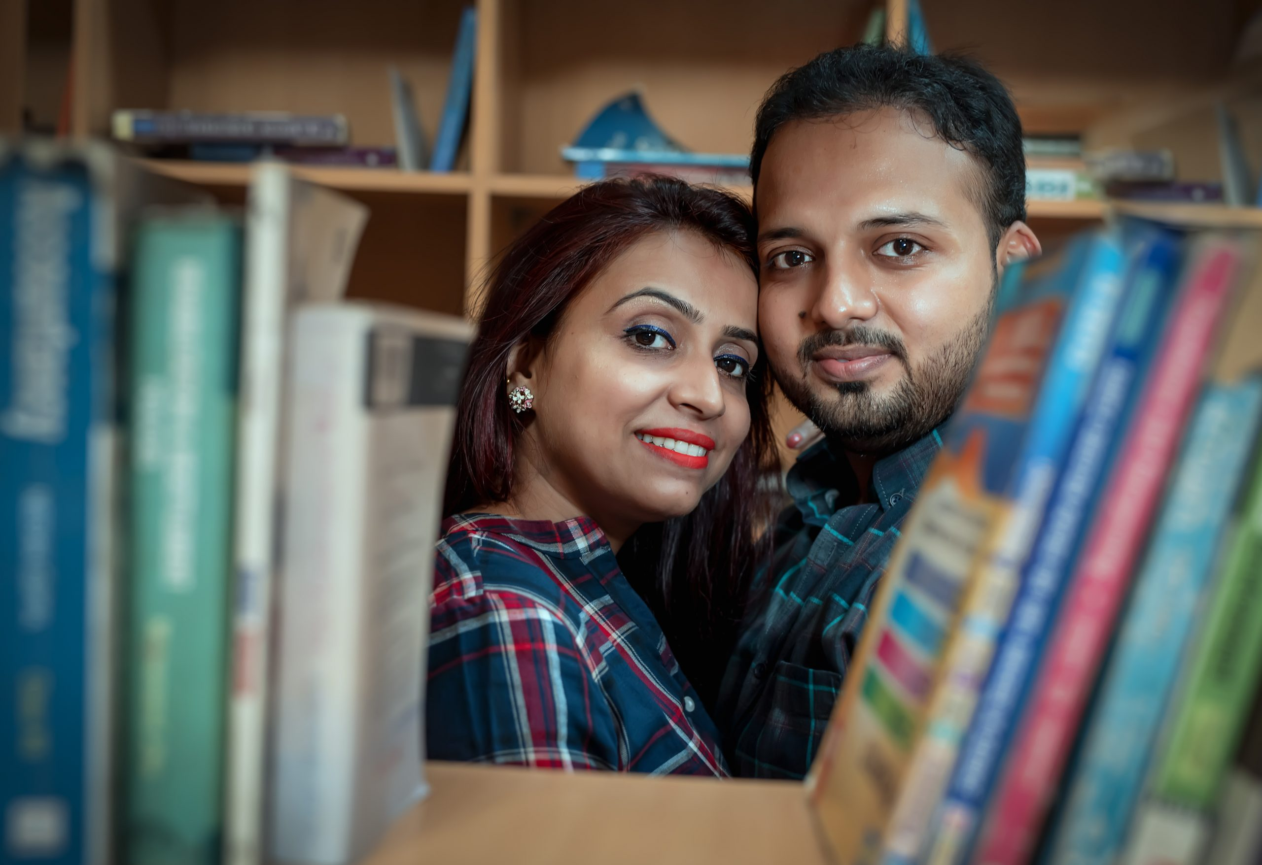 couple posing amidst books
