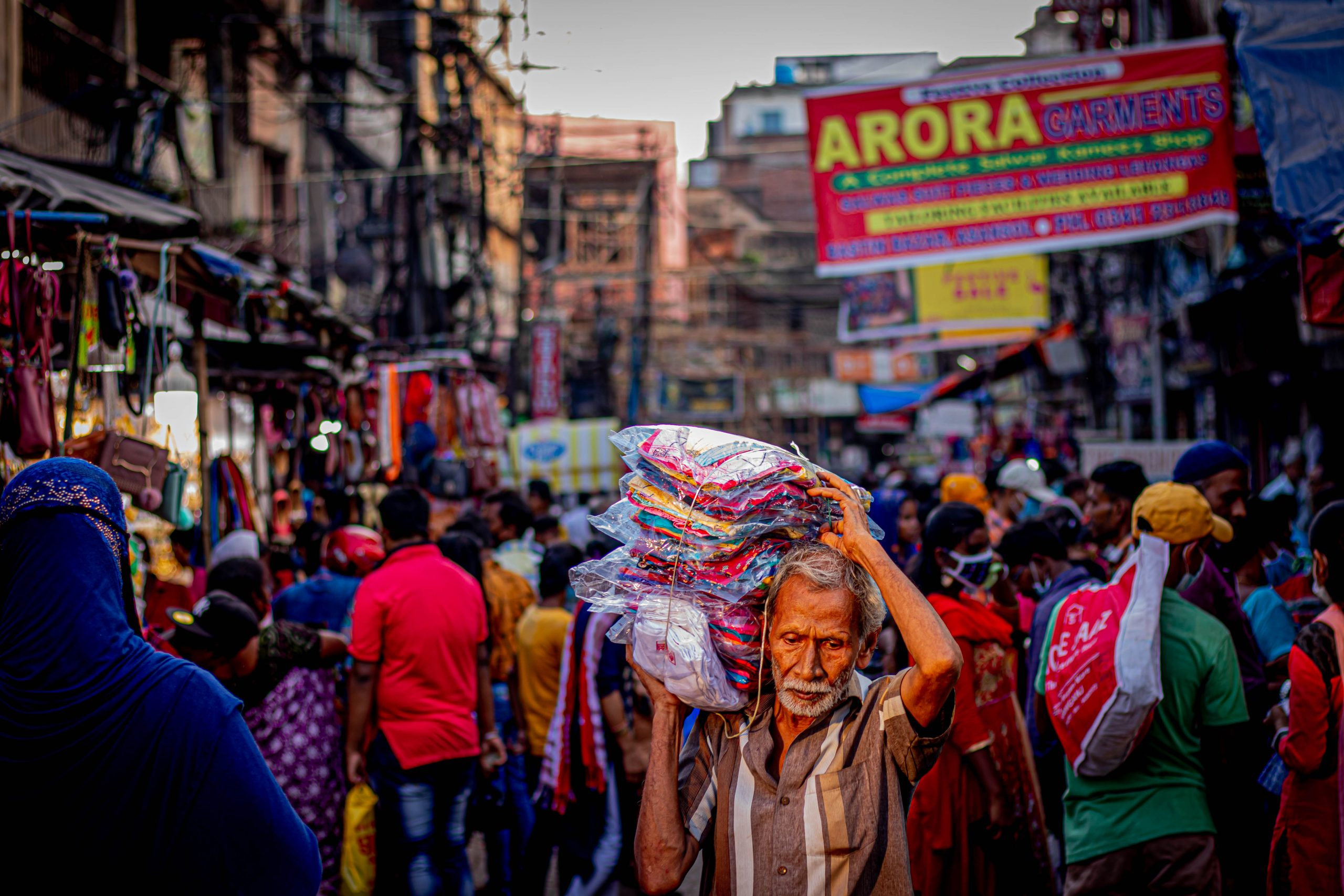 man carrying clothes in a market