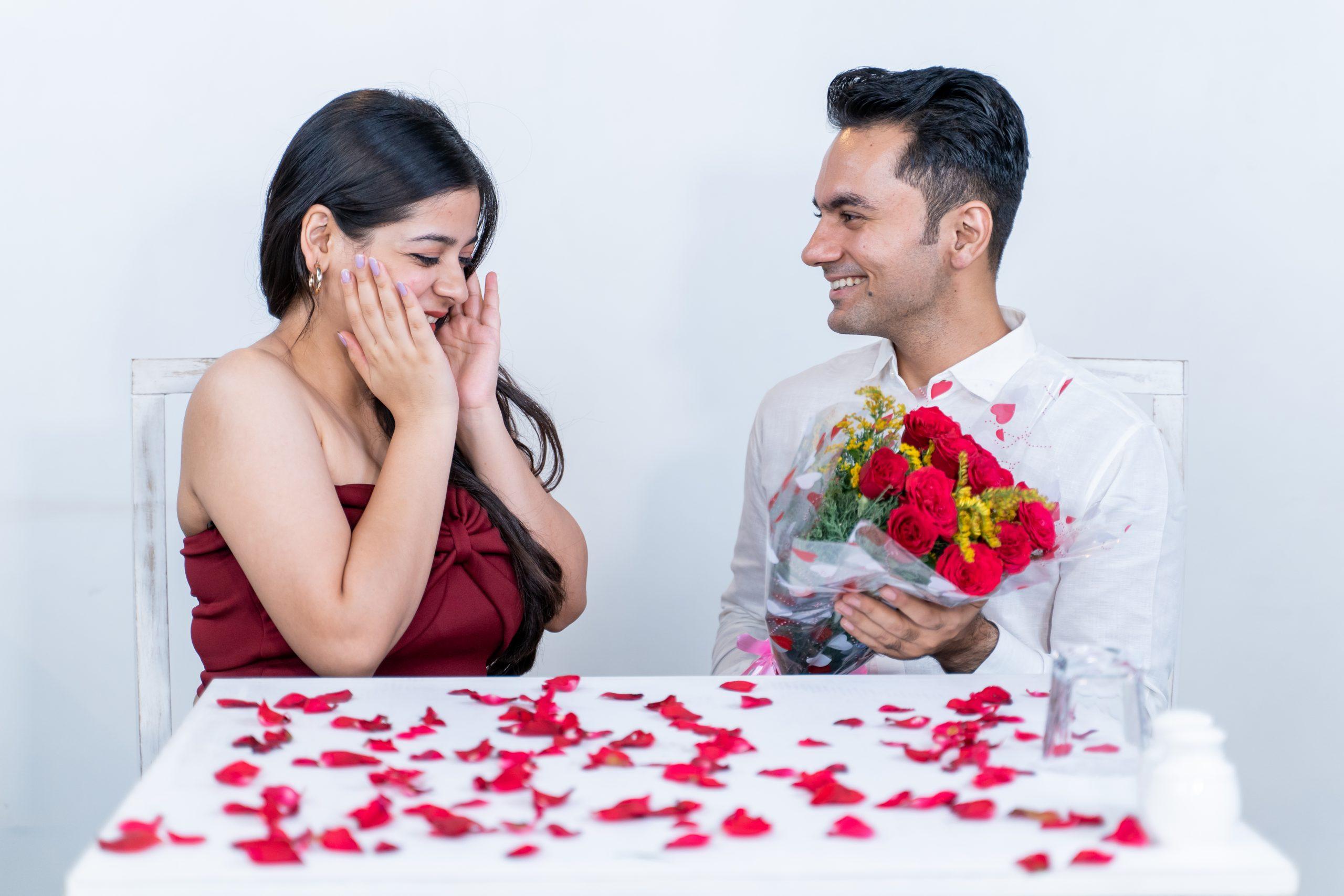 Boy surprising girlfriend with flowers