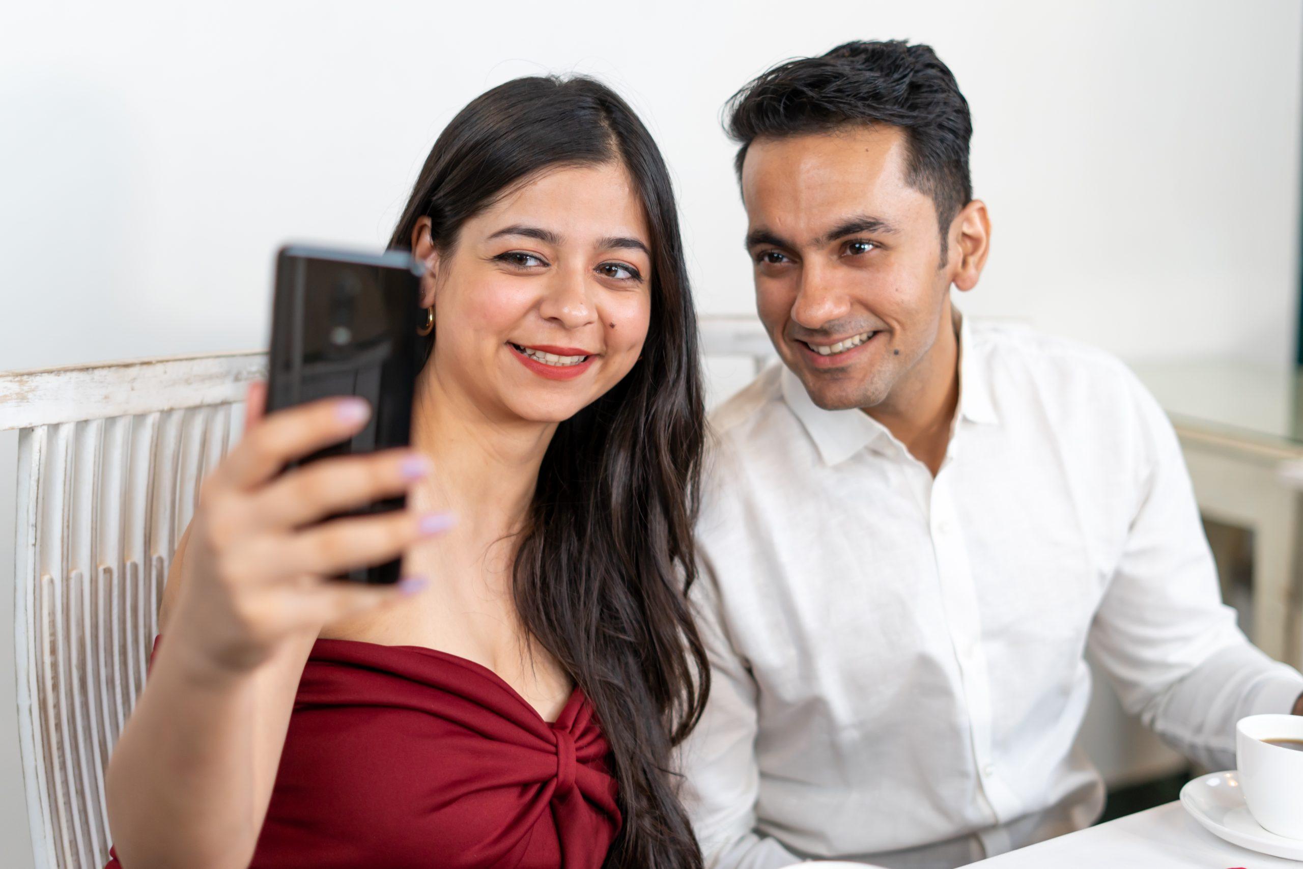 Boyfriend and girlfriend taking selfie in restaurant