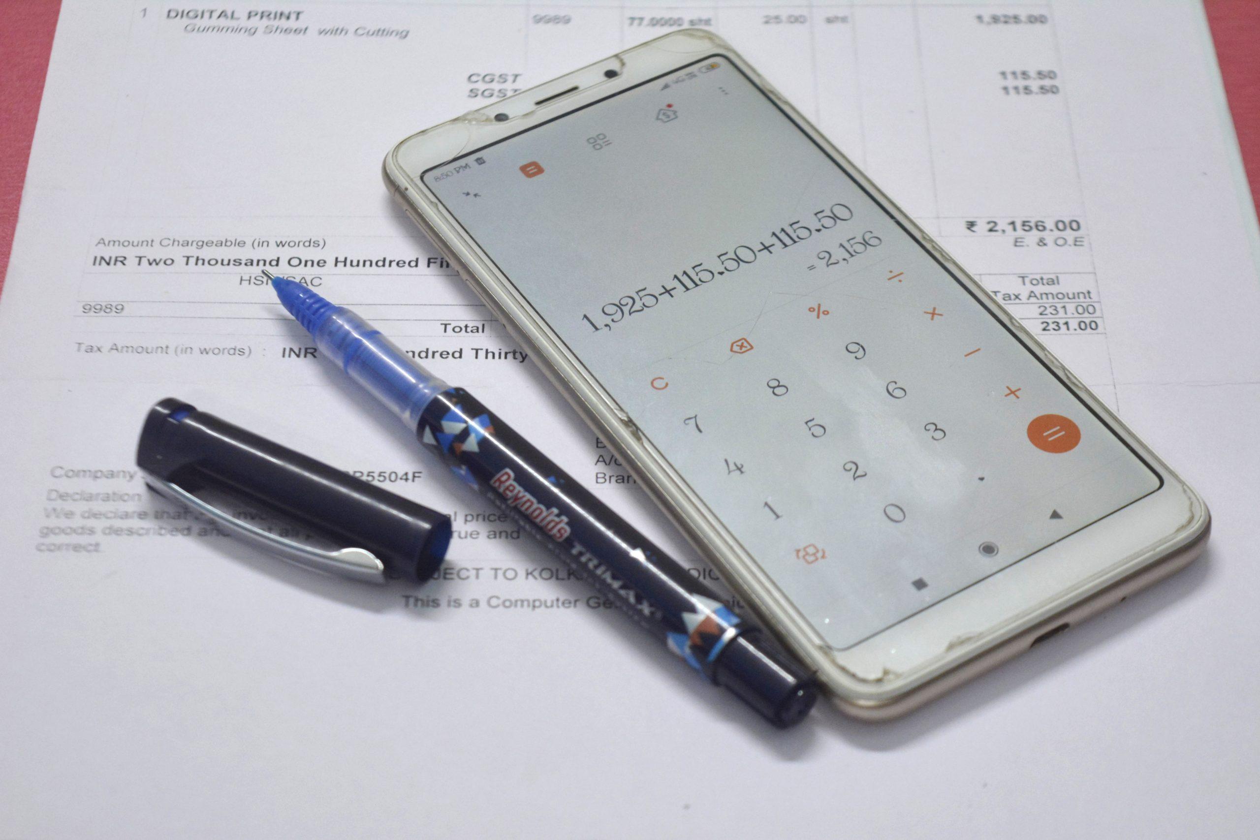 mobile calculator , pen and bill