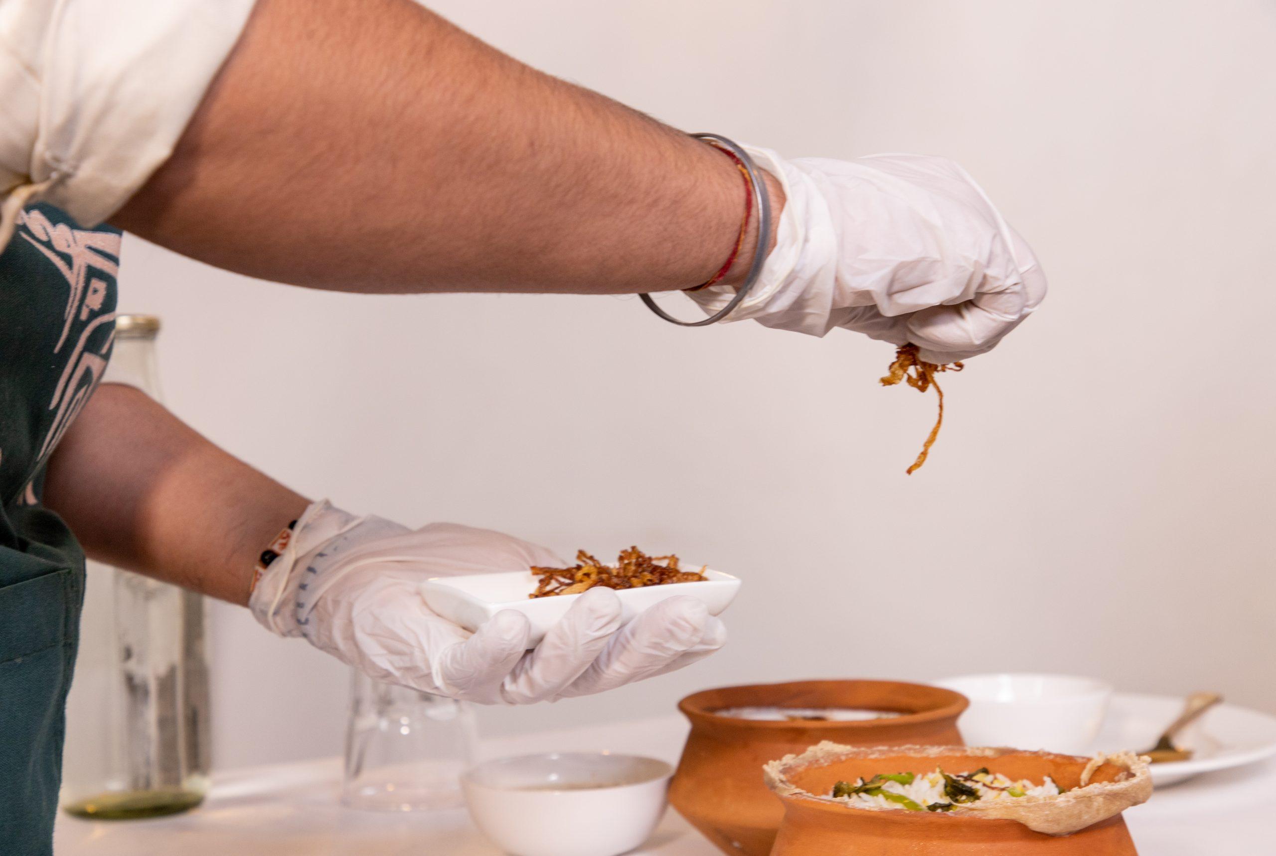 Chef garnishing biryani