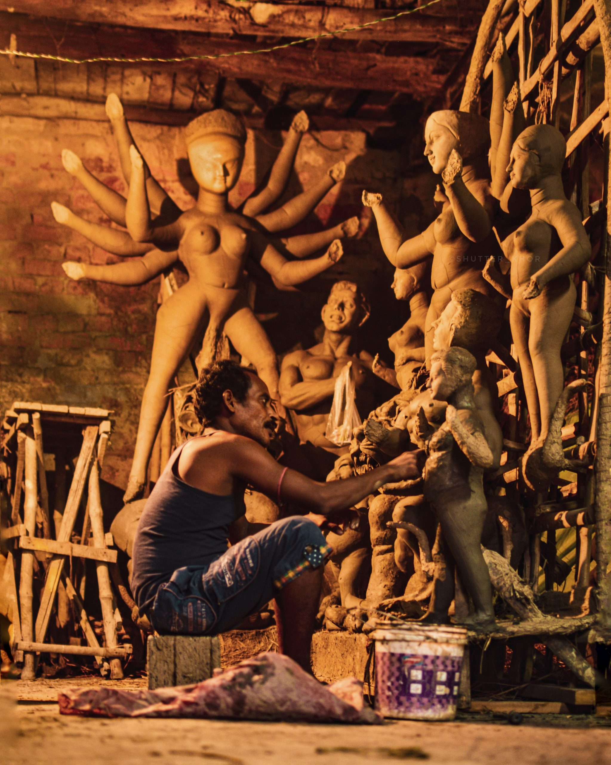 man carving statues