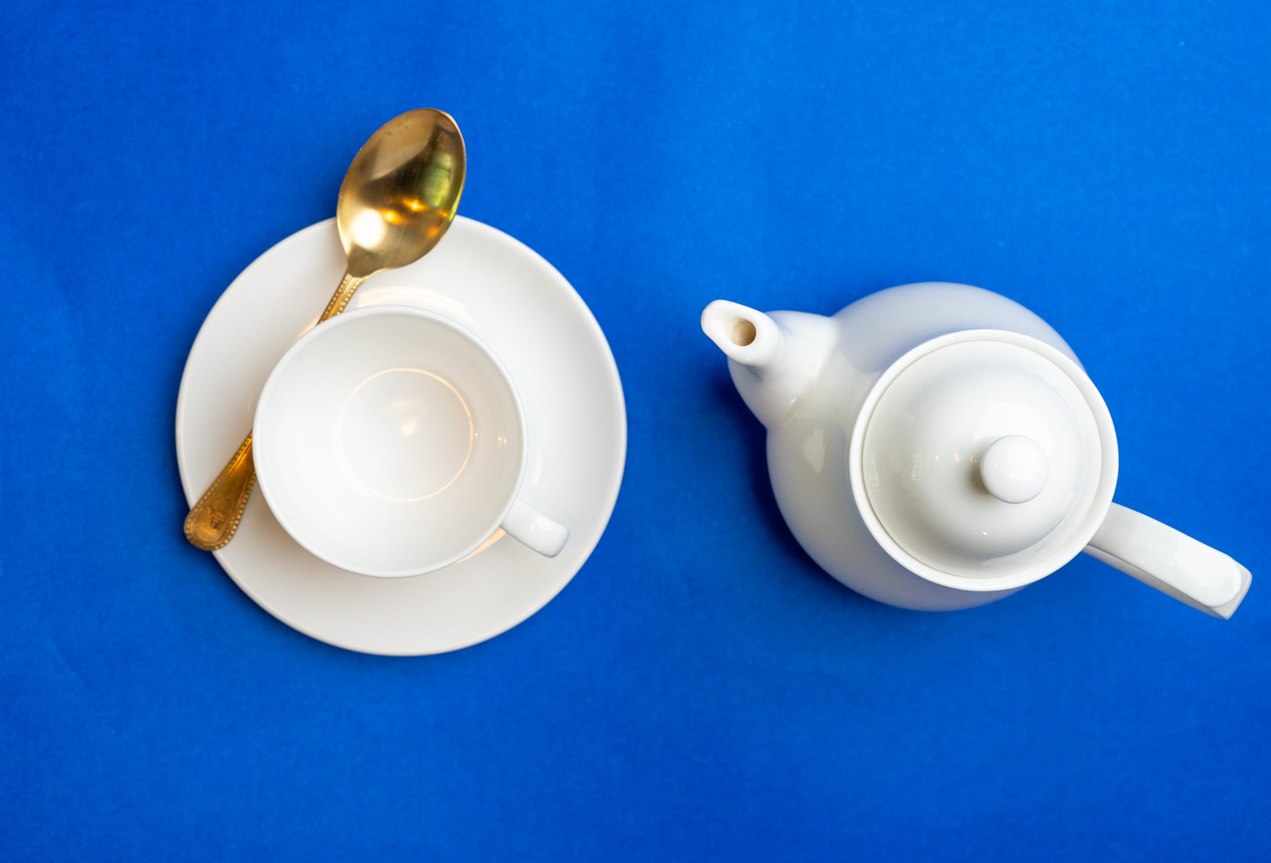 Cup and kettle on blue background