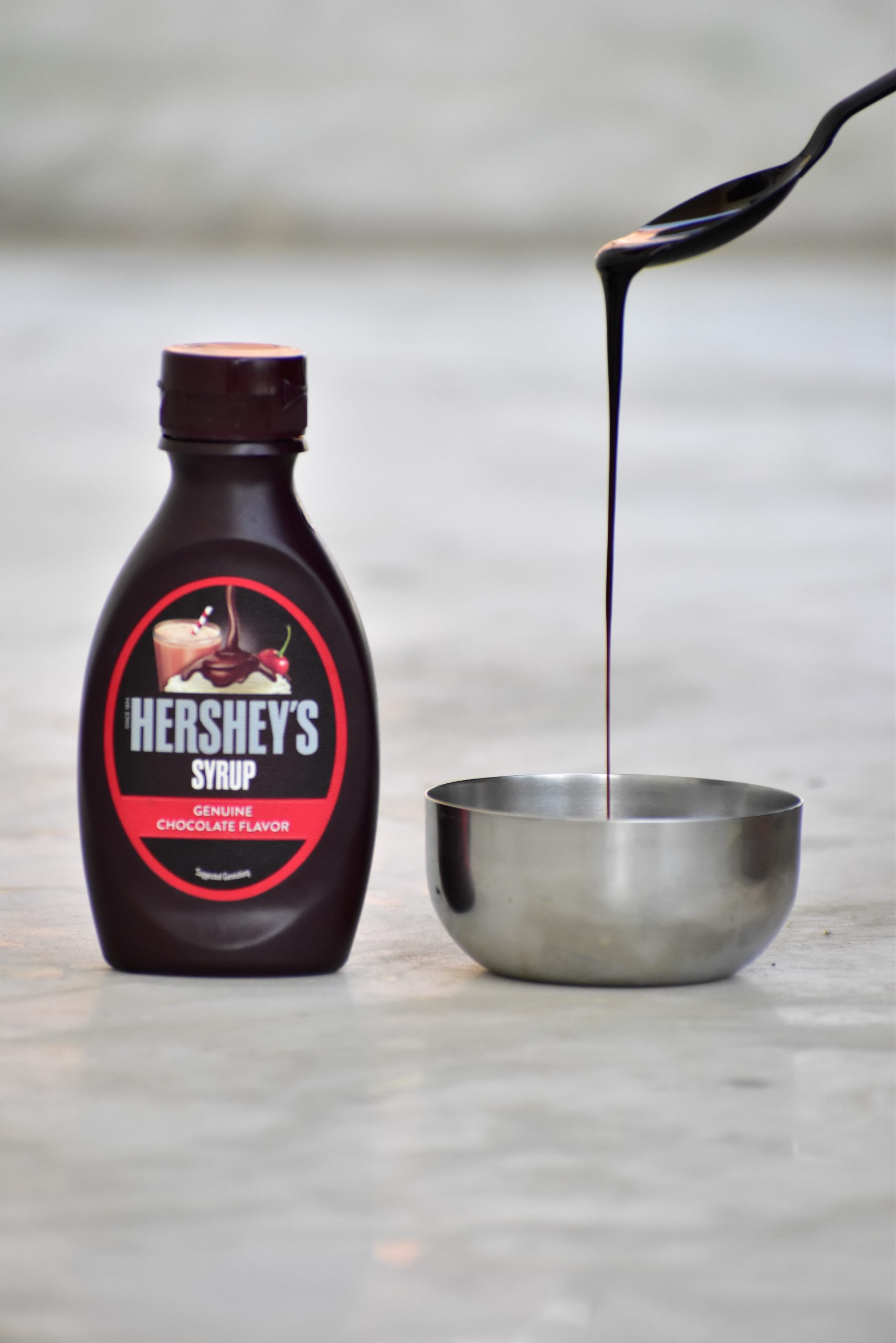dropping chocolate syrup in a bowl