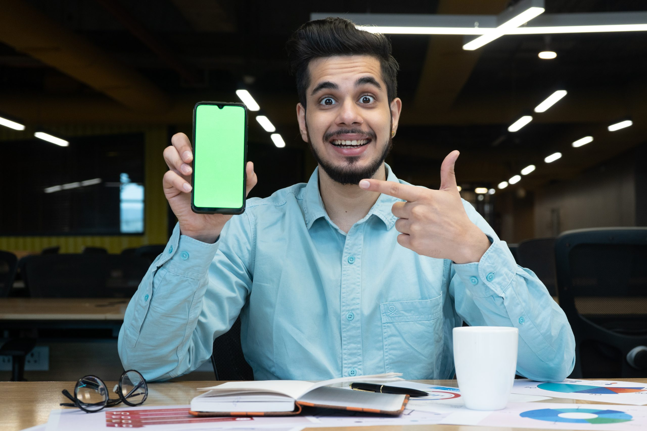Excited man pointing towards mobile screen