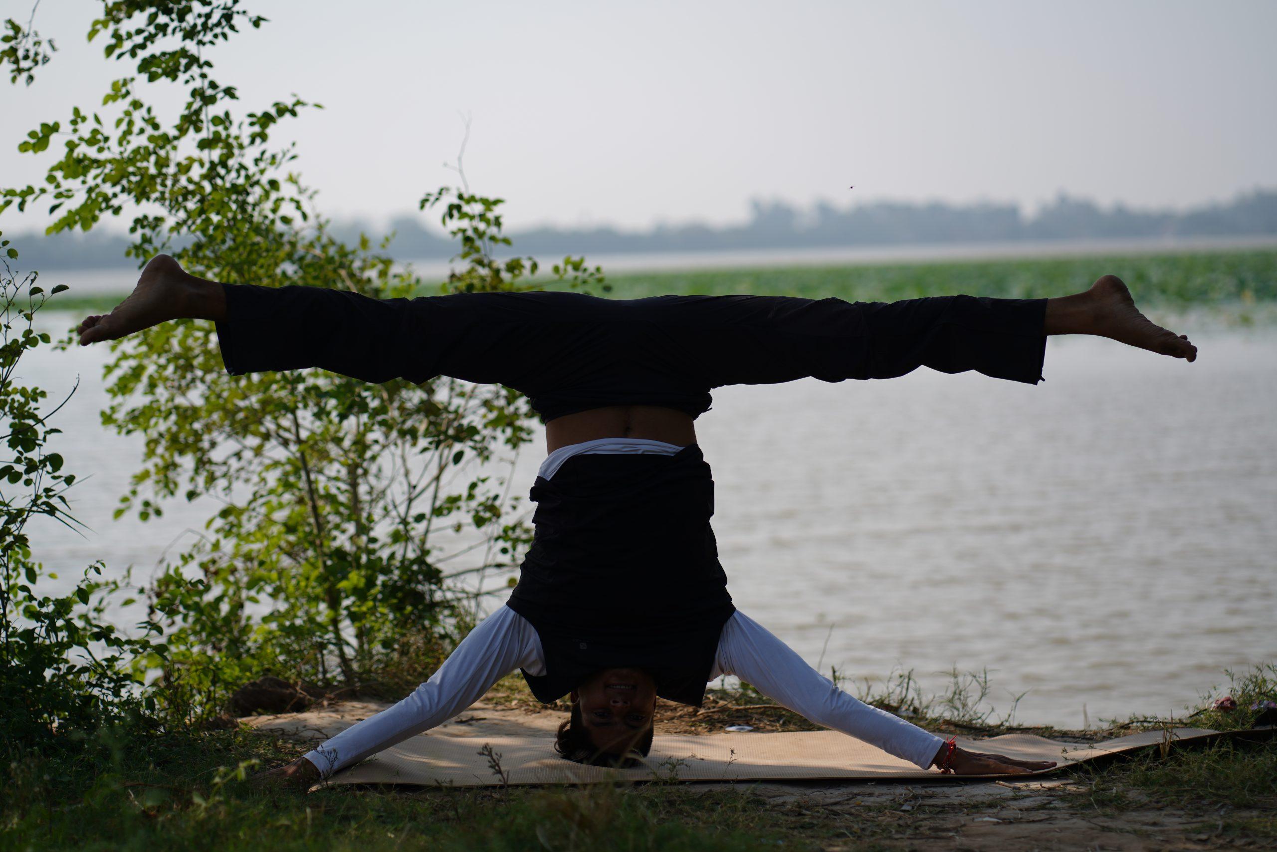 man doing yoga on lake side