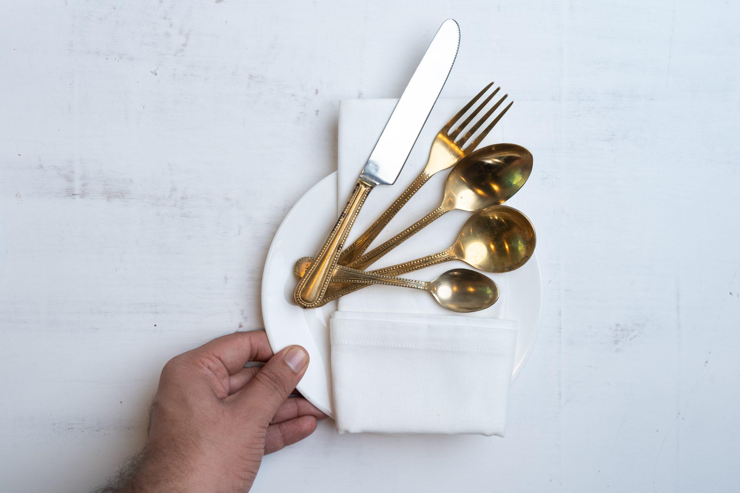Hand holding cutlery set