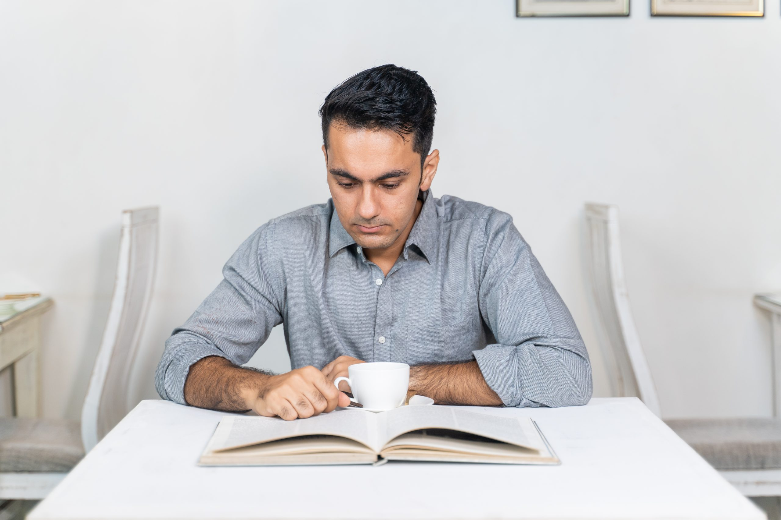 Handsome young man reading book in the cafe