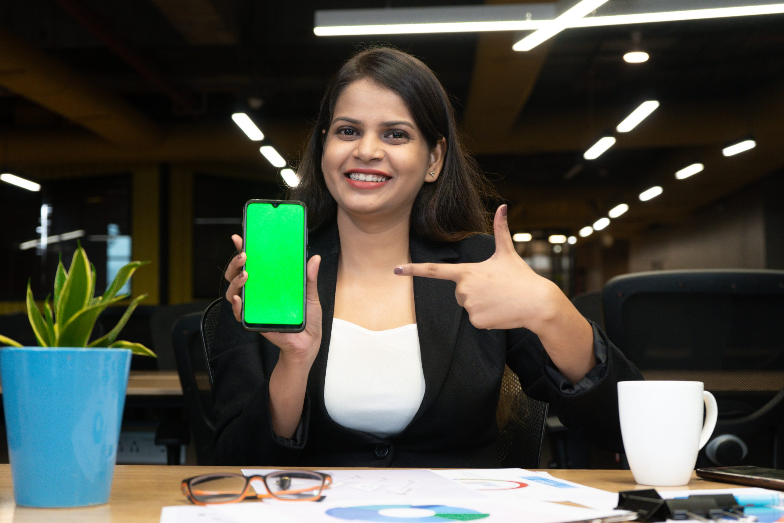 Happy CEO pointing towards with green screen mobile