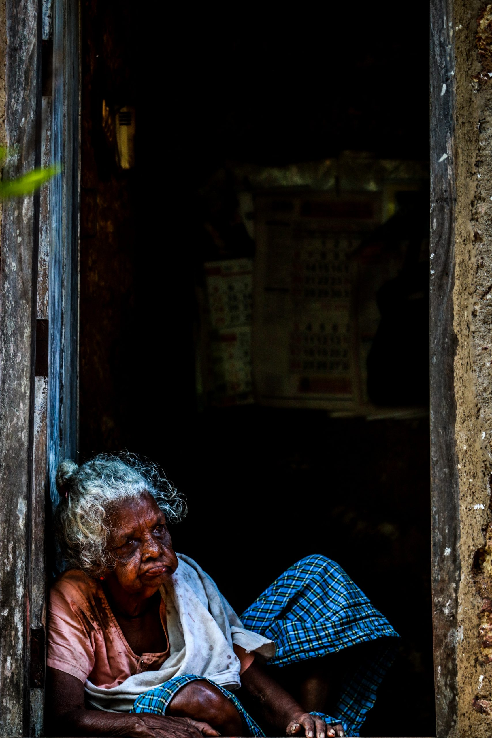 An old lady sit at house door