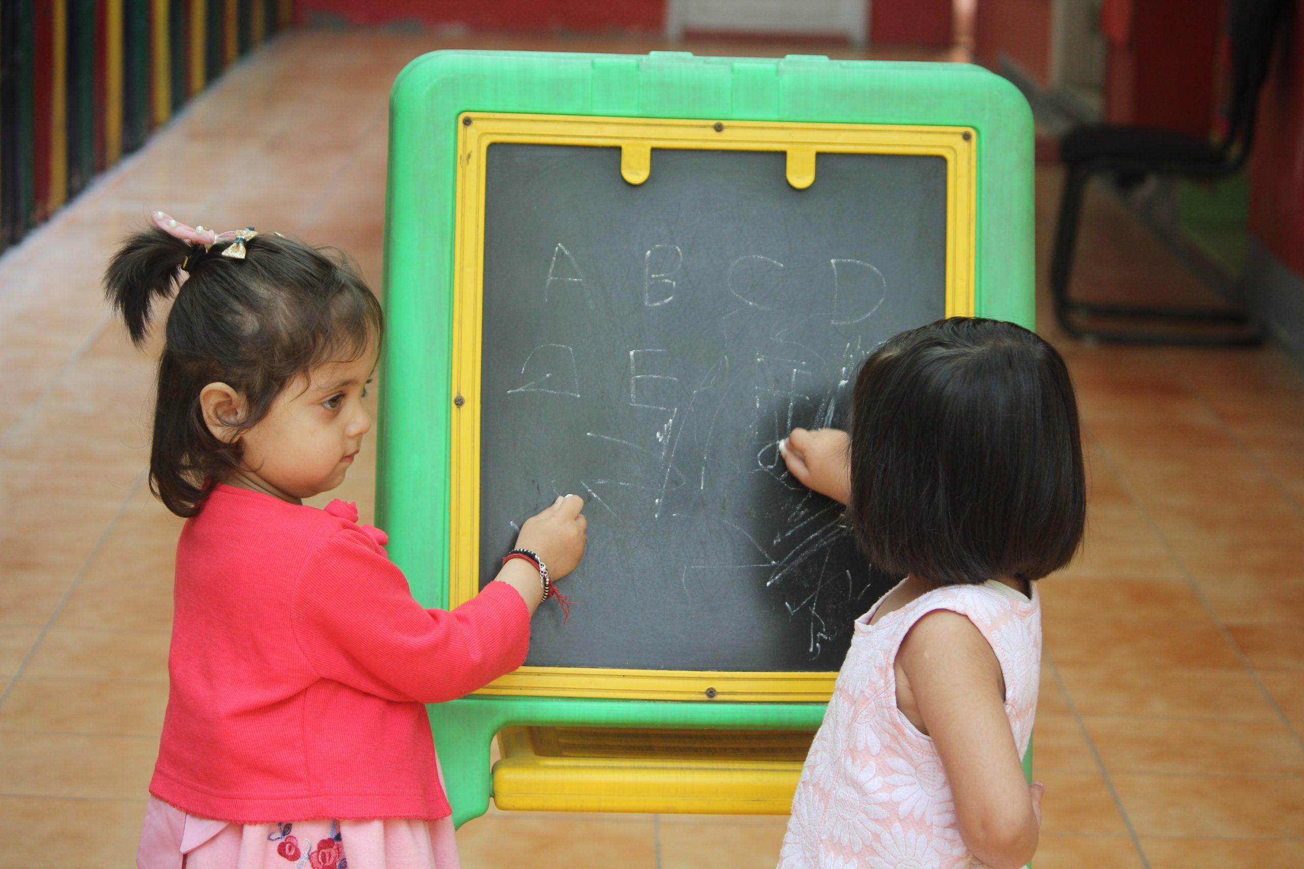 Kids writing on a small blackboard