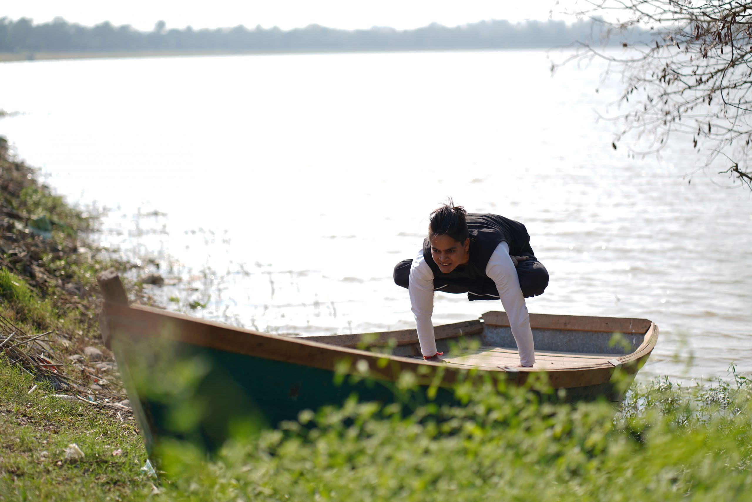 man doing yoga by the lake