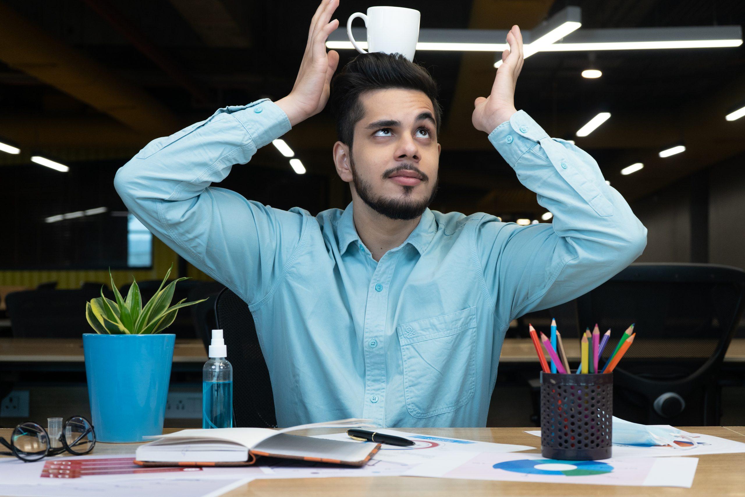 Man balancing coffee mug on head