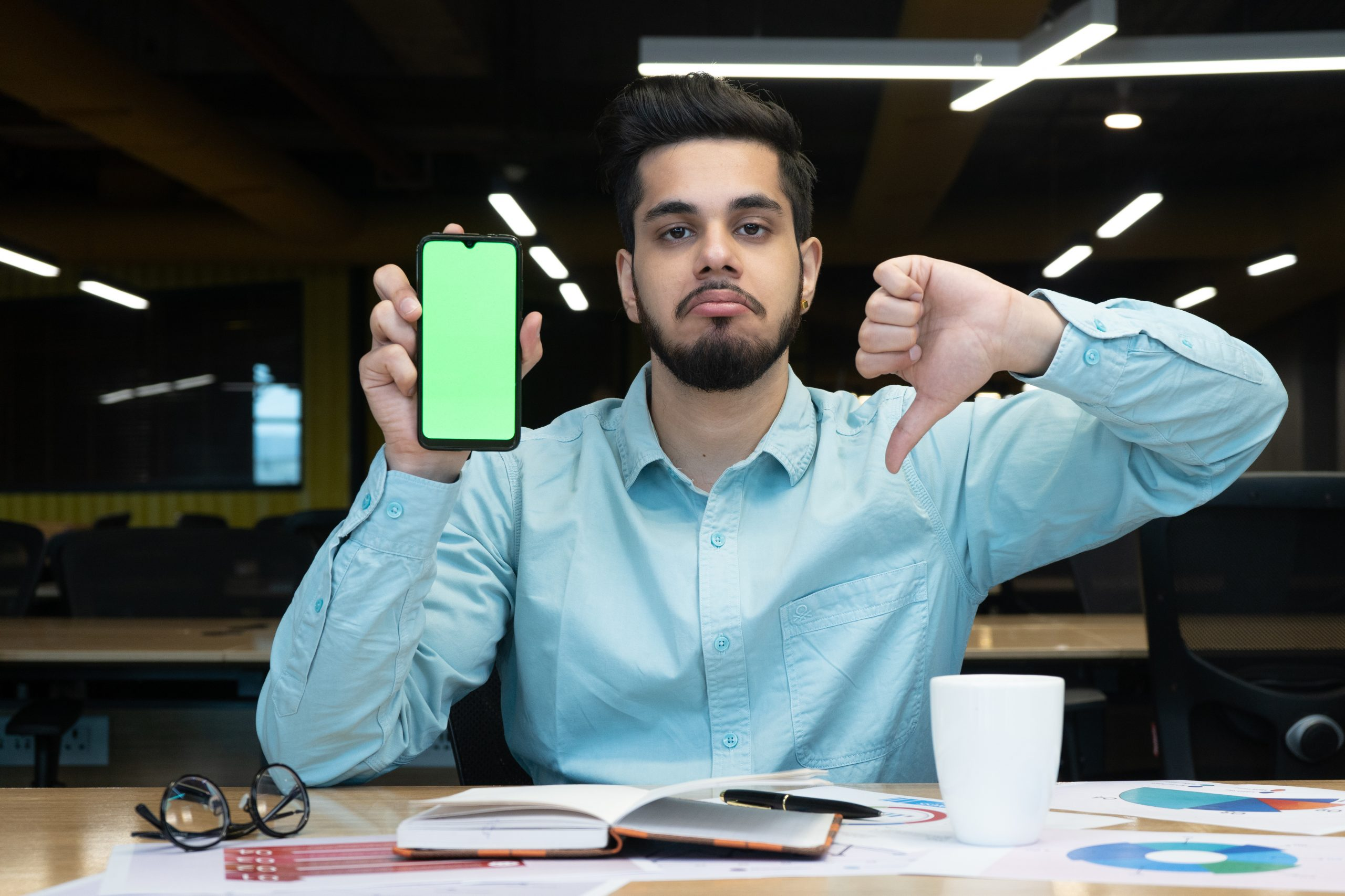 Man showing thumbs down with mobile screen