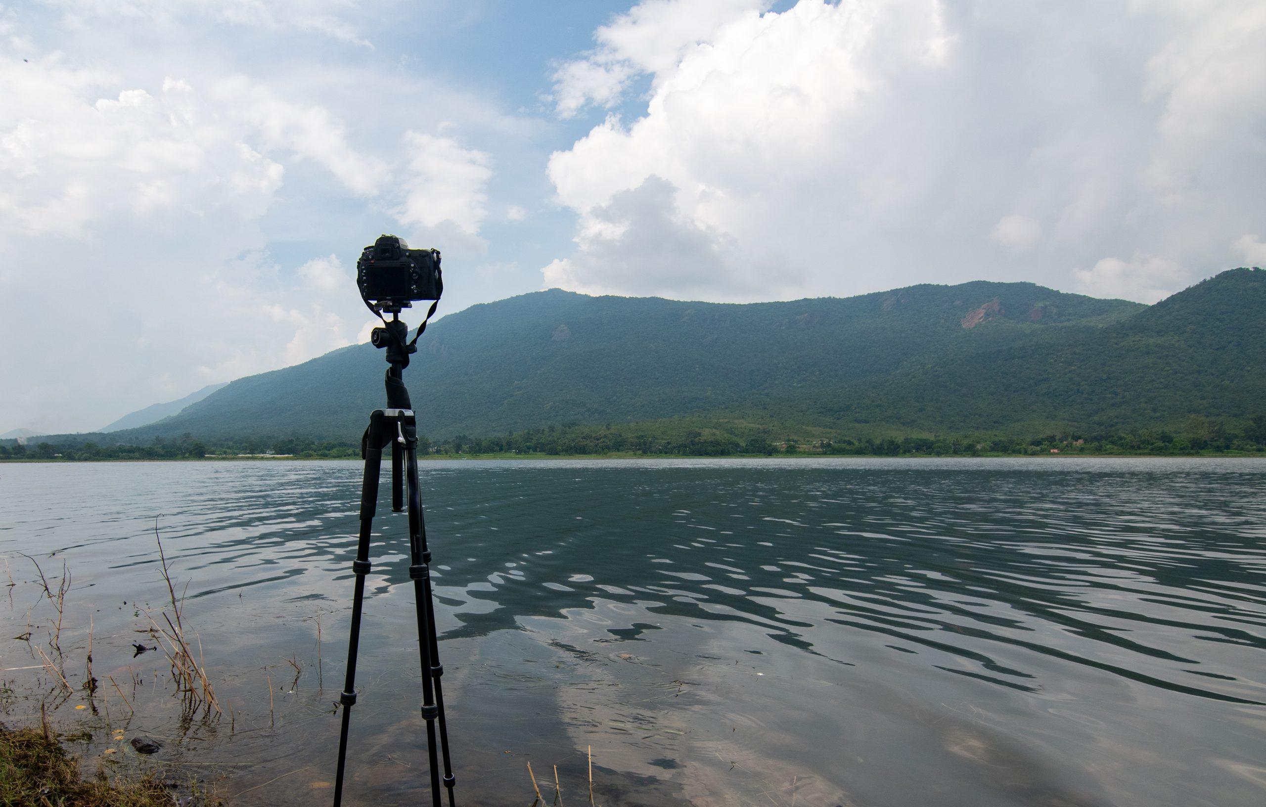A tripod camera beside a river