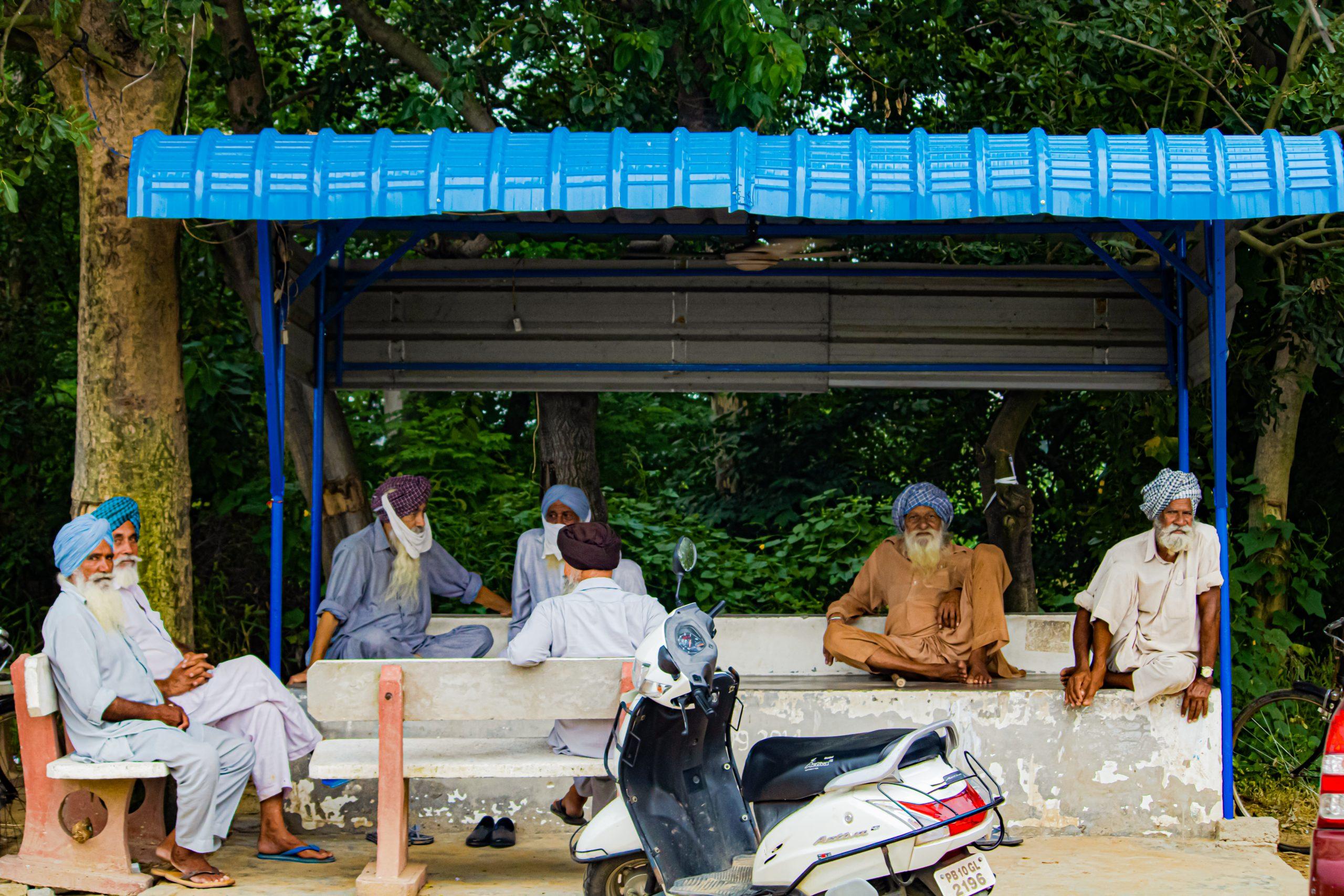 Old men sit under a rain shelter