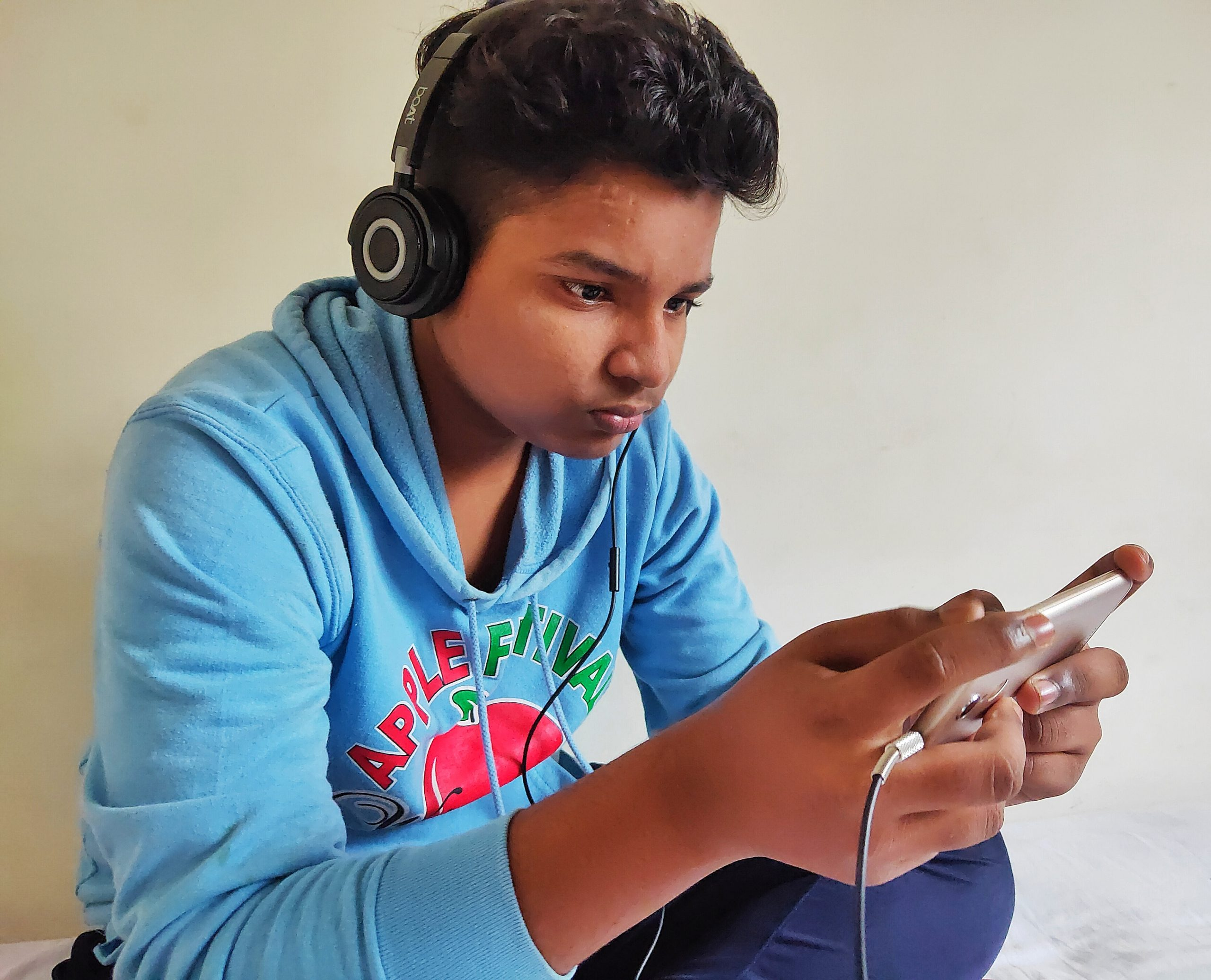 boy using mobile and headphones