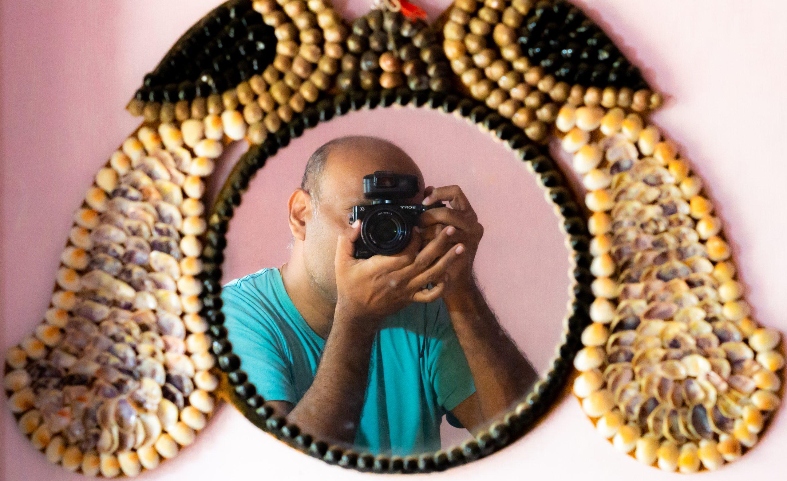 A man taking photo through mirror