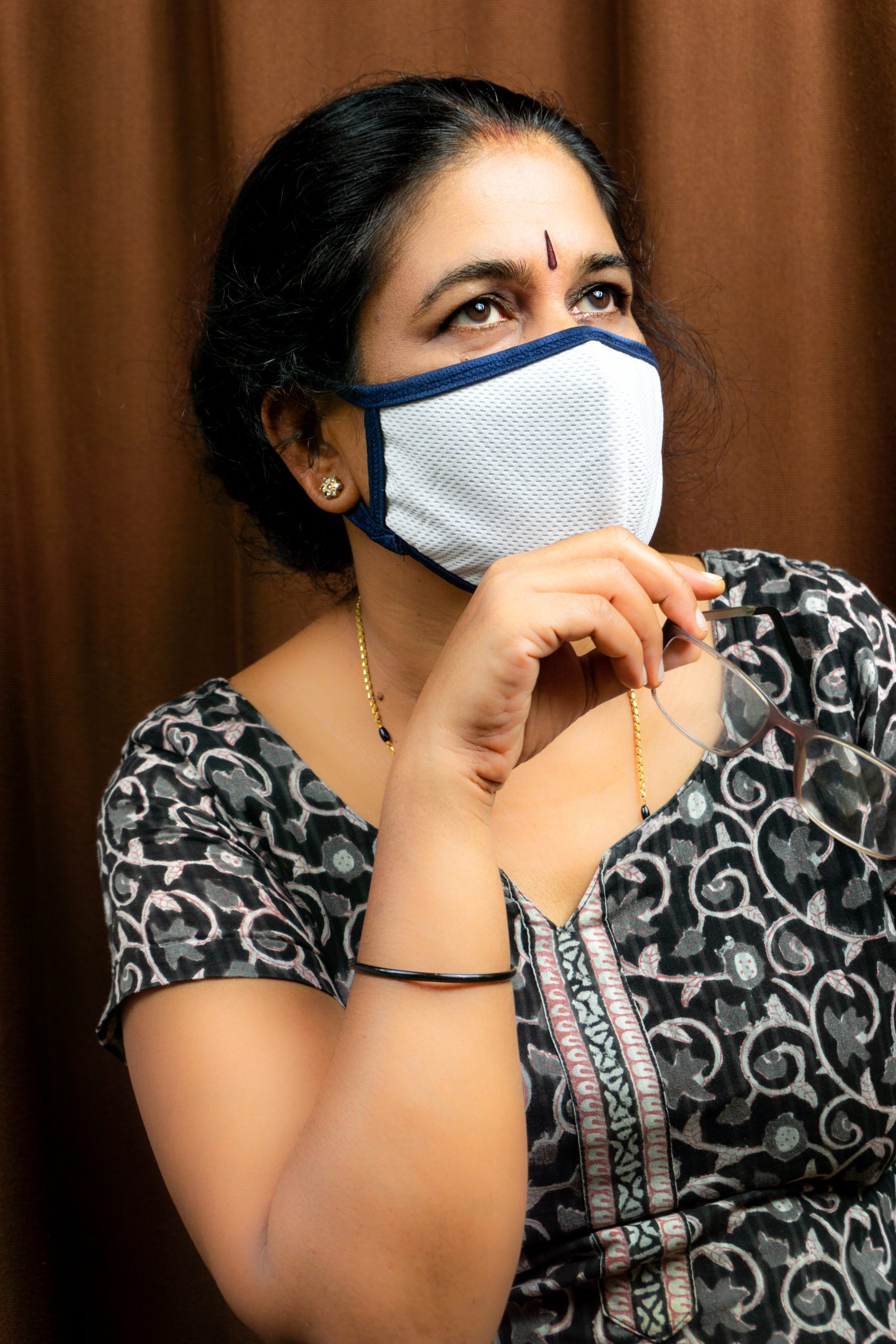 woman with mask holding spects