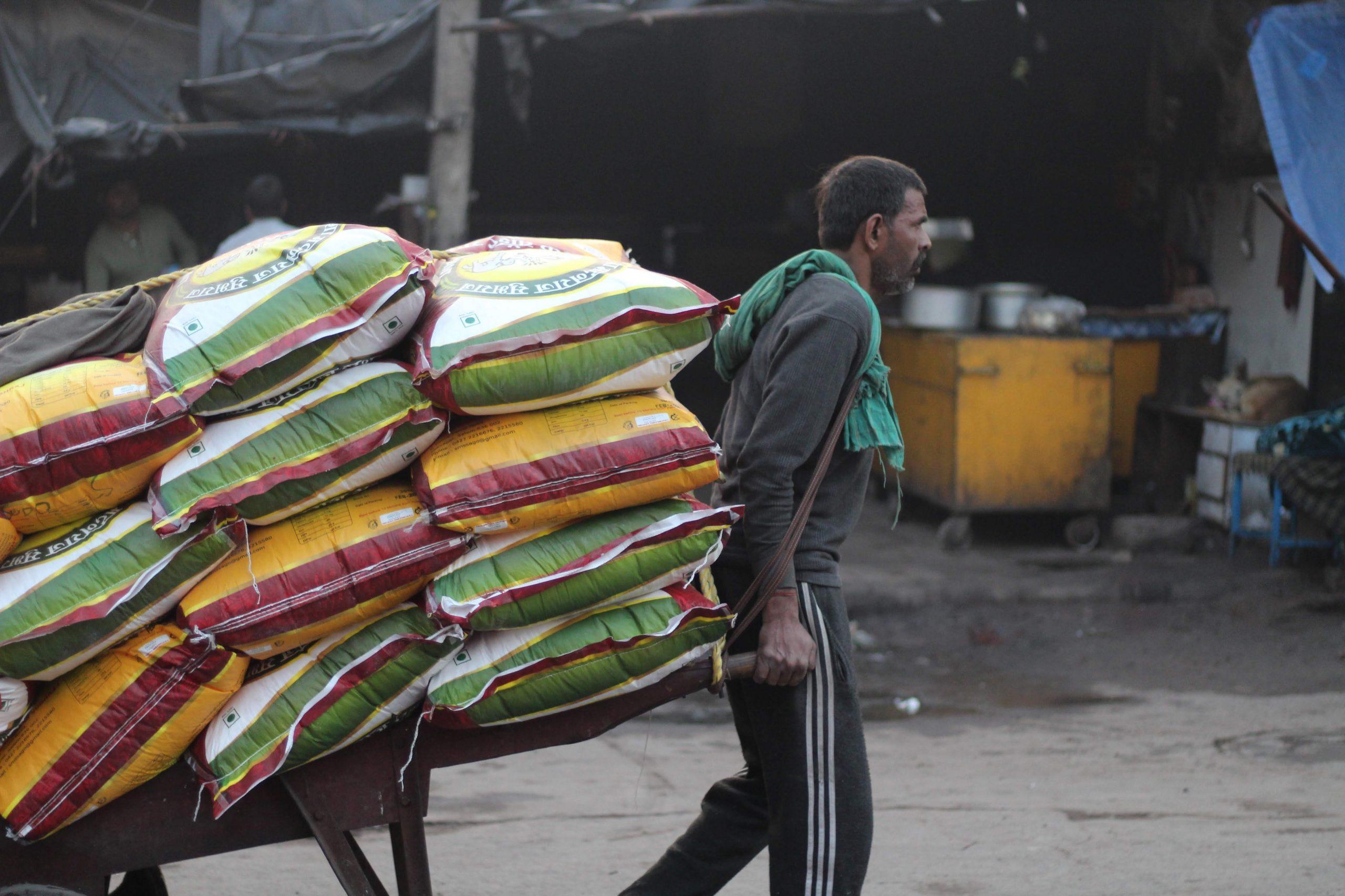man carrying sacs on a cart